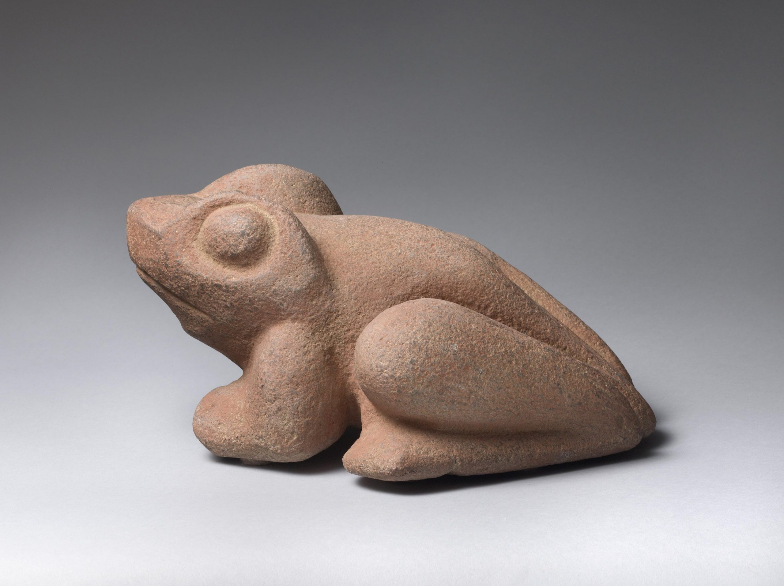 Stone sculpture of a perched frog.