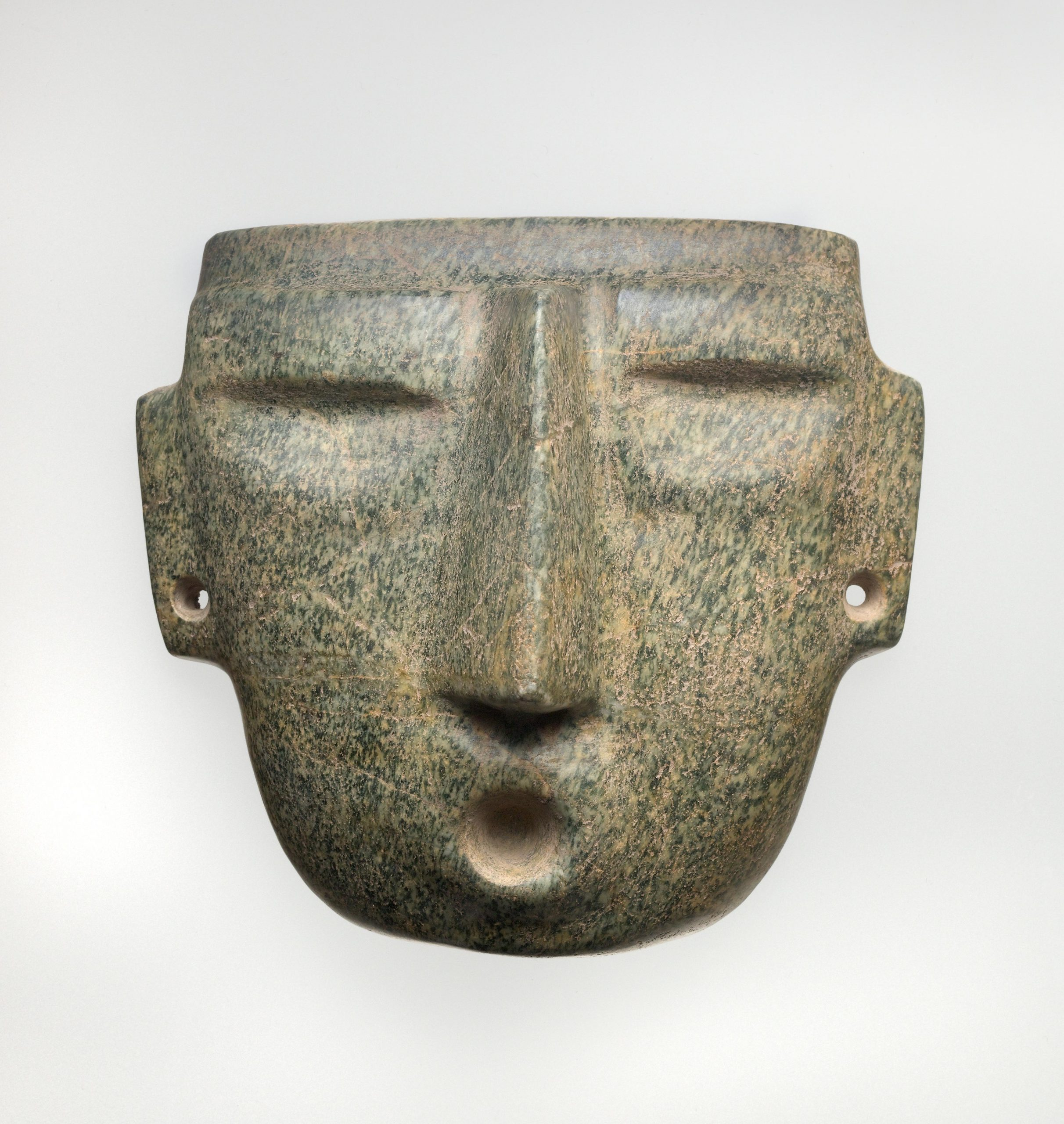 A mask with naturalistic features, including an open mouth, carved-out eyes, and spool holes in the nose and ears.