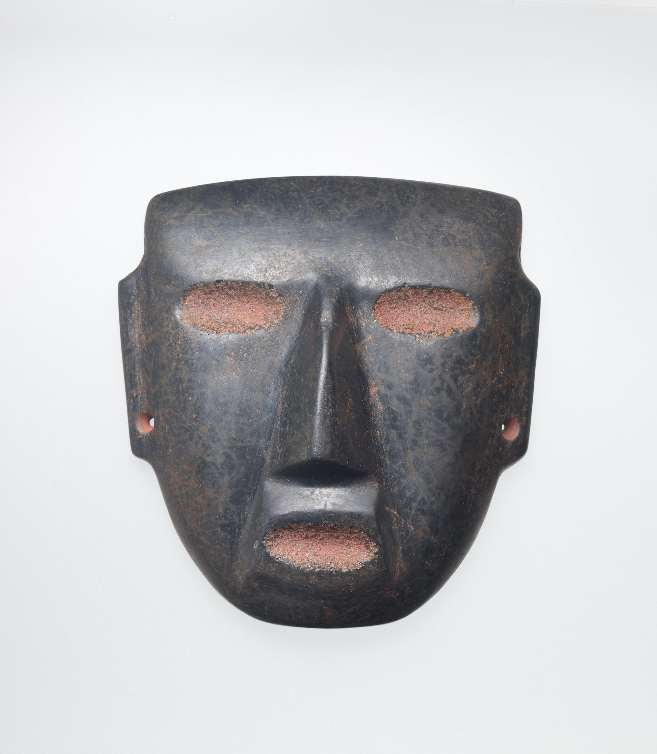 Black stone mask with red eyes and mouth, drilled ear spools, and a triangular nose.