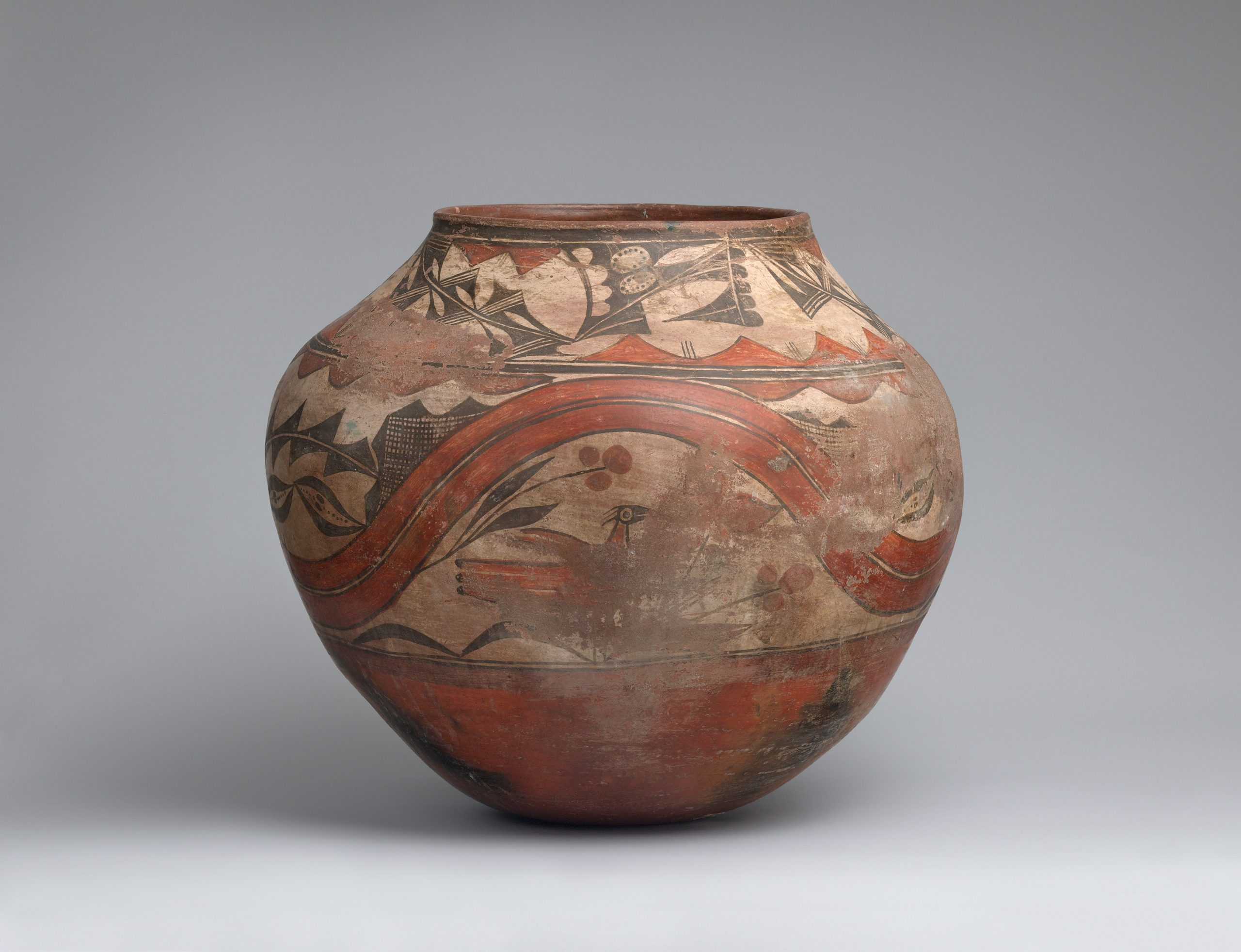 A Zia jar decorated with two bands of designs, including birds, flowers, plants, and geometric shapes.
