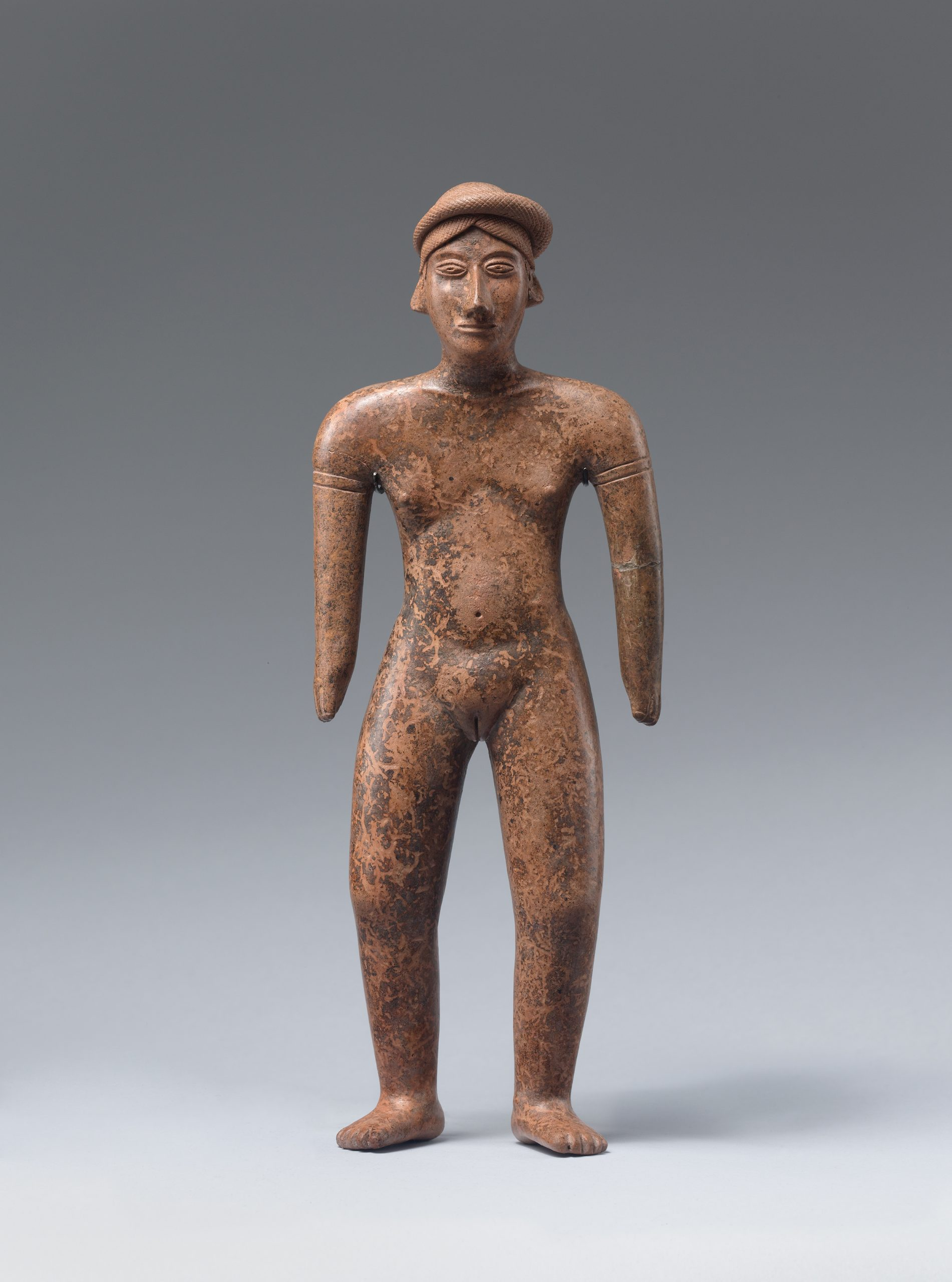 Pendant of a figure with both hands on their head and a large round hole in the chest.