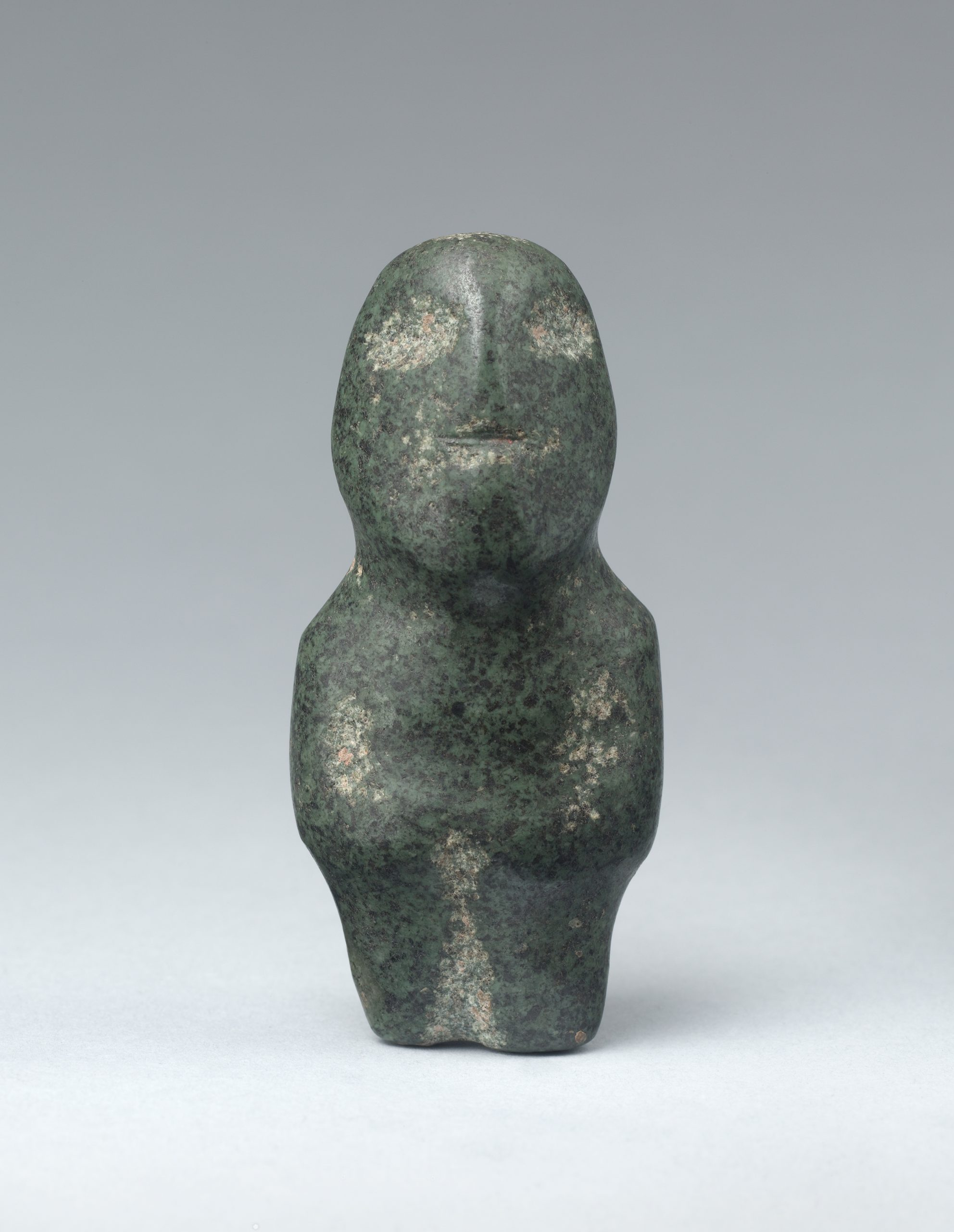 A stylized stone sculpture of a standing female figure with her arms at her side, her left leg has been broken off.