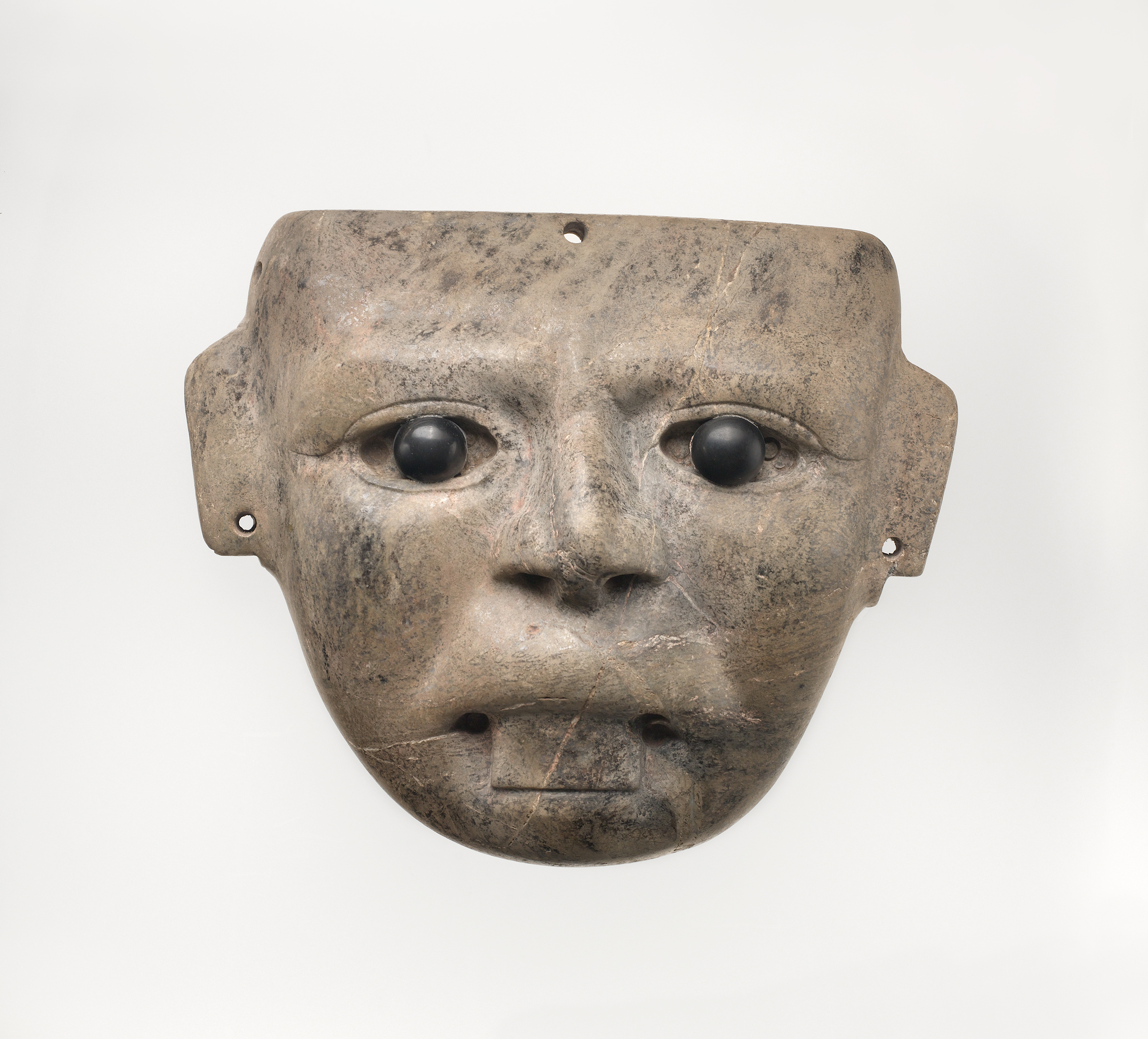 Stylistic stone mask with inlaid black eyes and stuck out tongue.