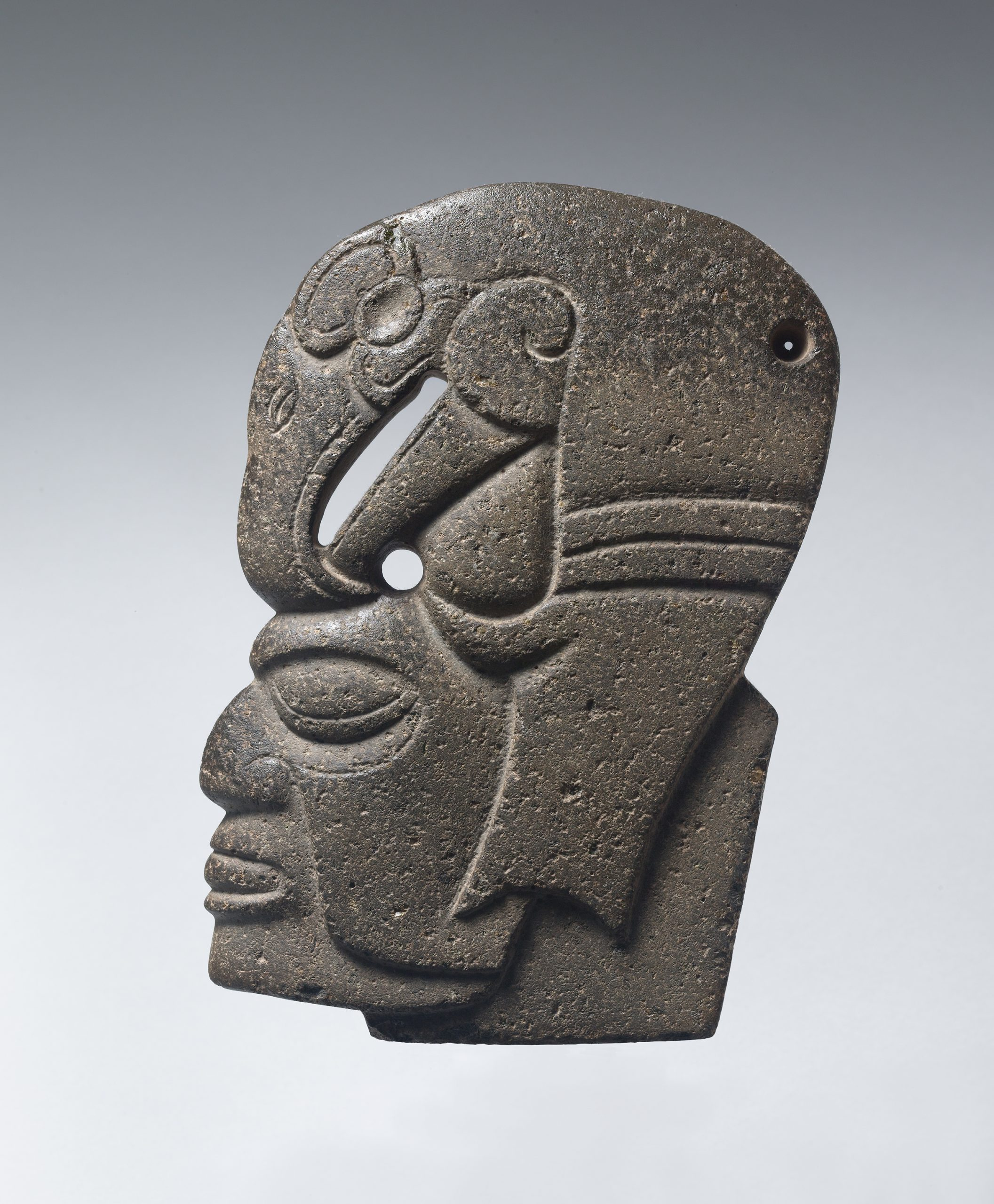 Stone sculpture of an abstracted standing figure with carved facial features and arms at the torso.