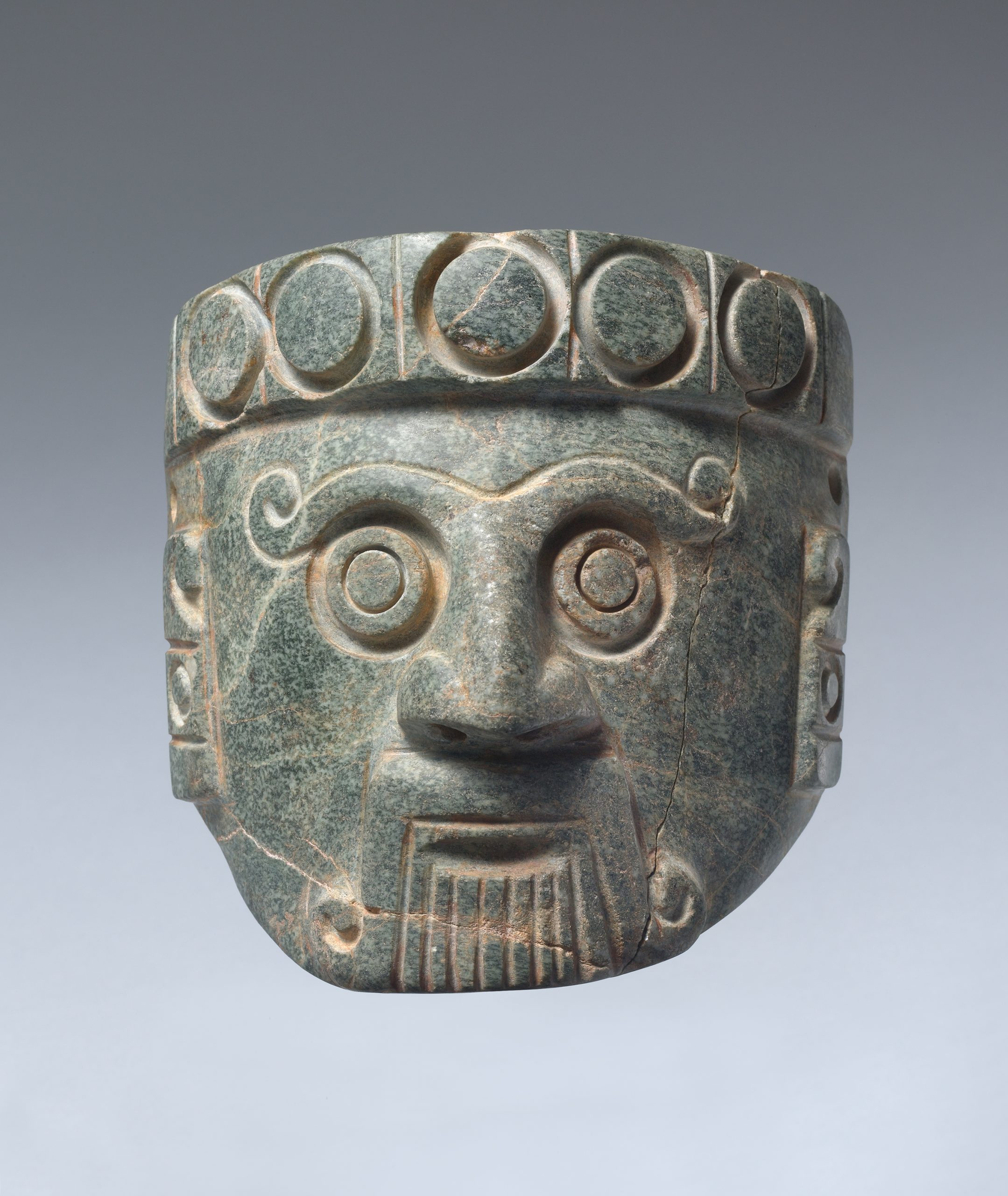 Stone head of a rain god with large bulging eyes and long fangs emerging from curled lips.