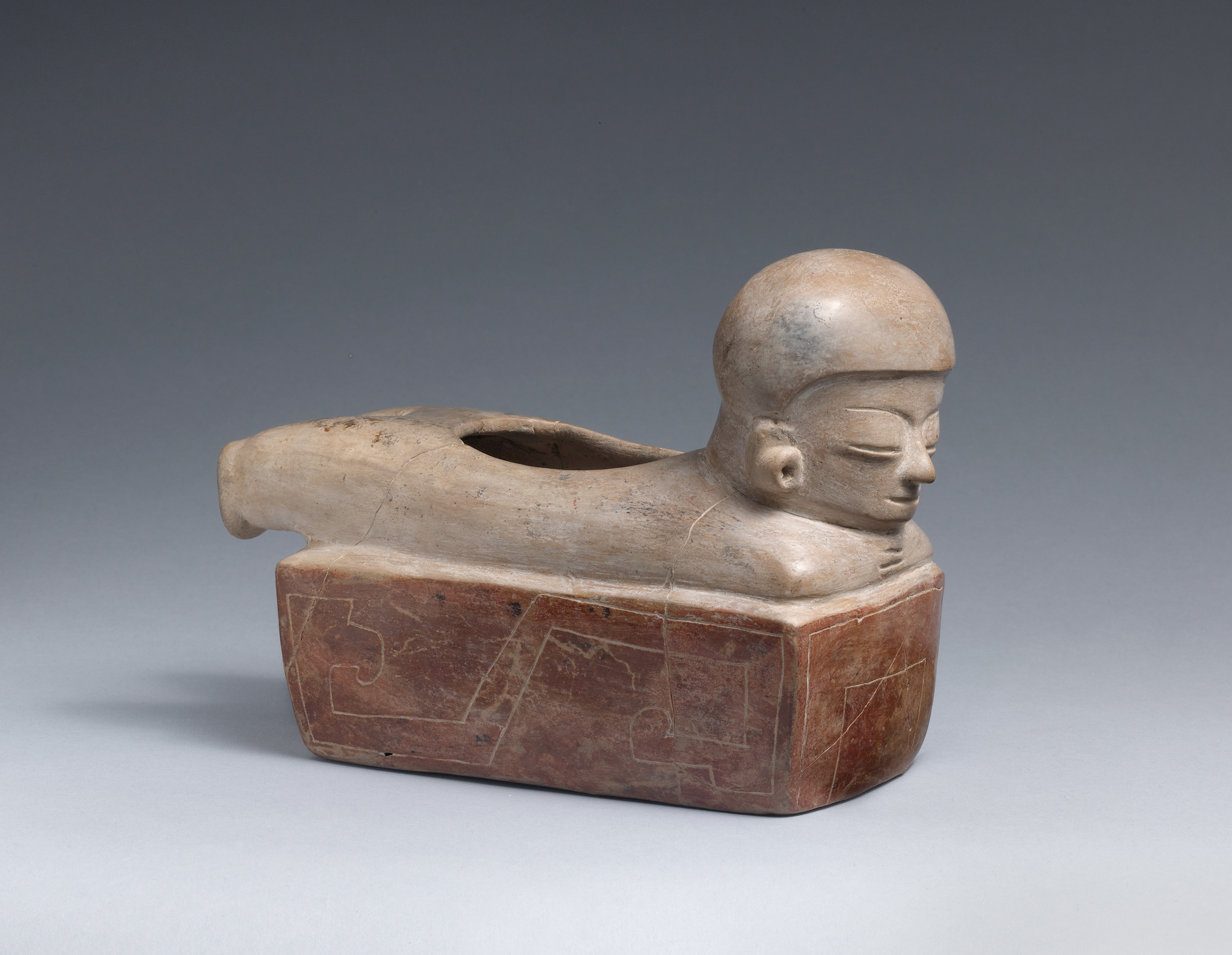 Ceramic vessel of a human figure with a helmet and earplugs, laying on their stomach.