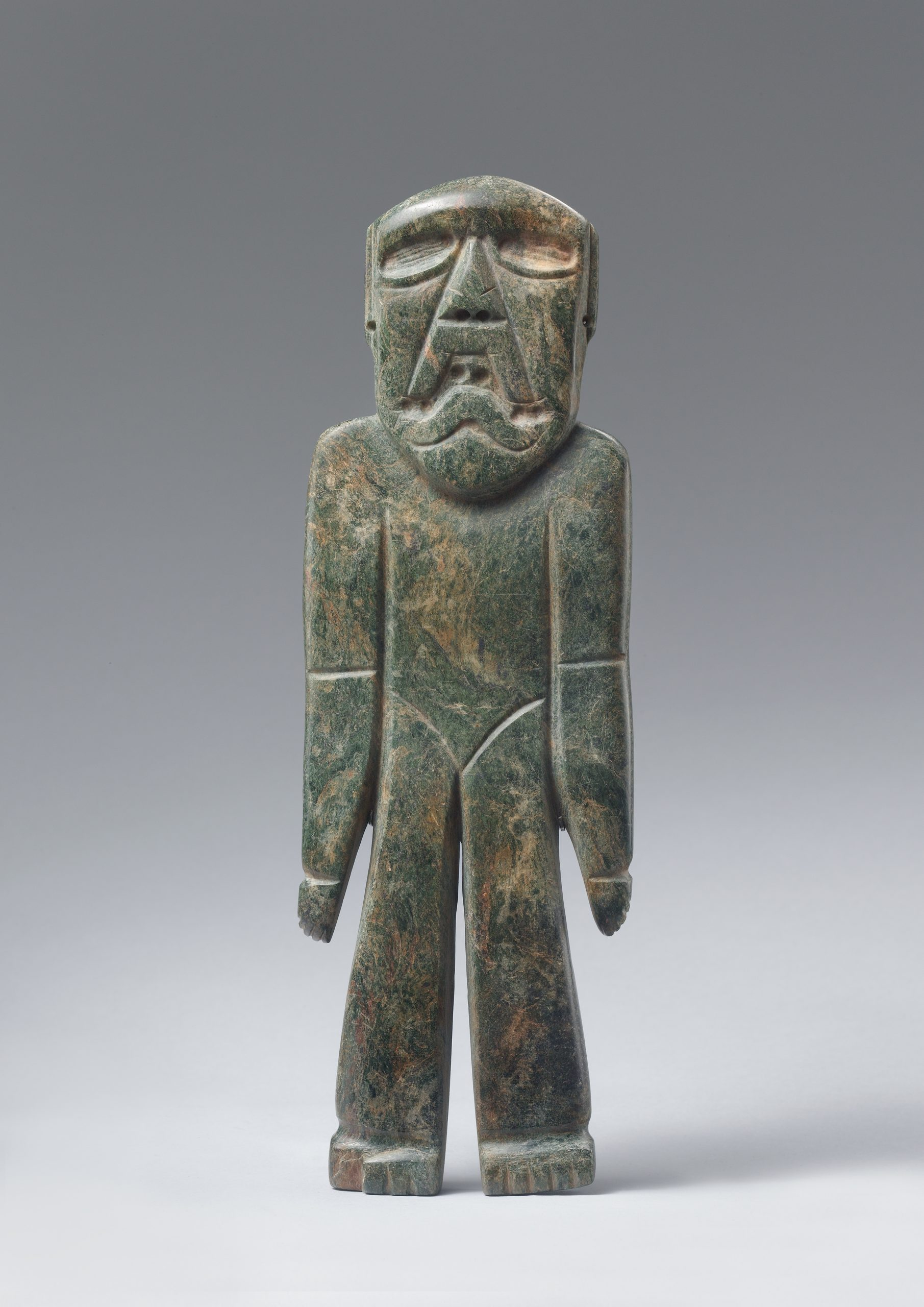 Standing stone figure with large eyes, triangular face, and hands resting at the sides.