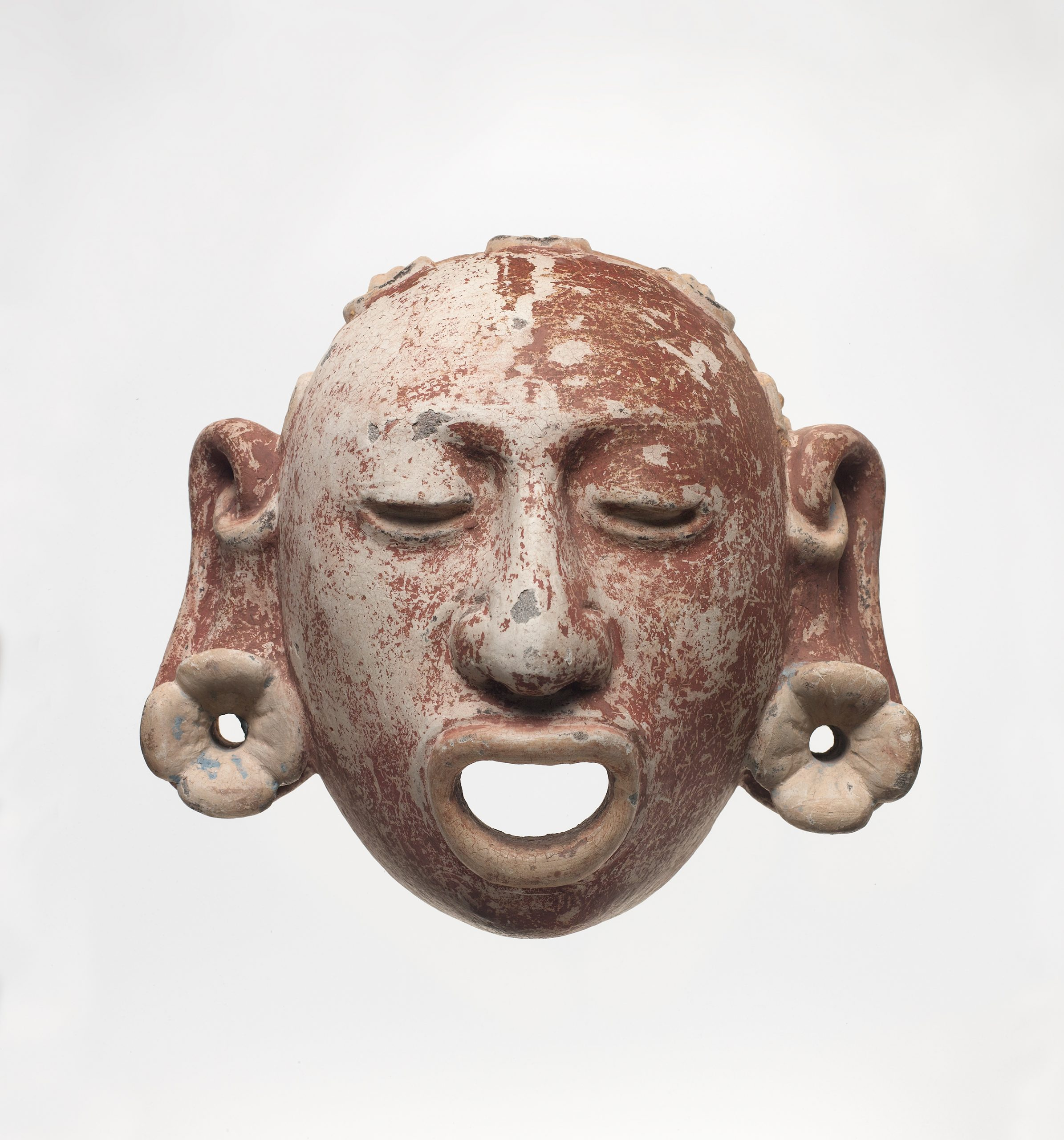 Decorative stone mask of an Aztec god with open mouth, closed eyes, and large pierced ears.