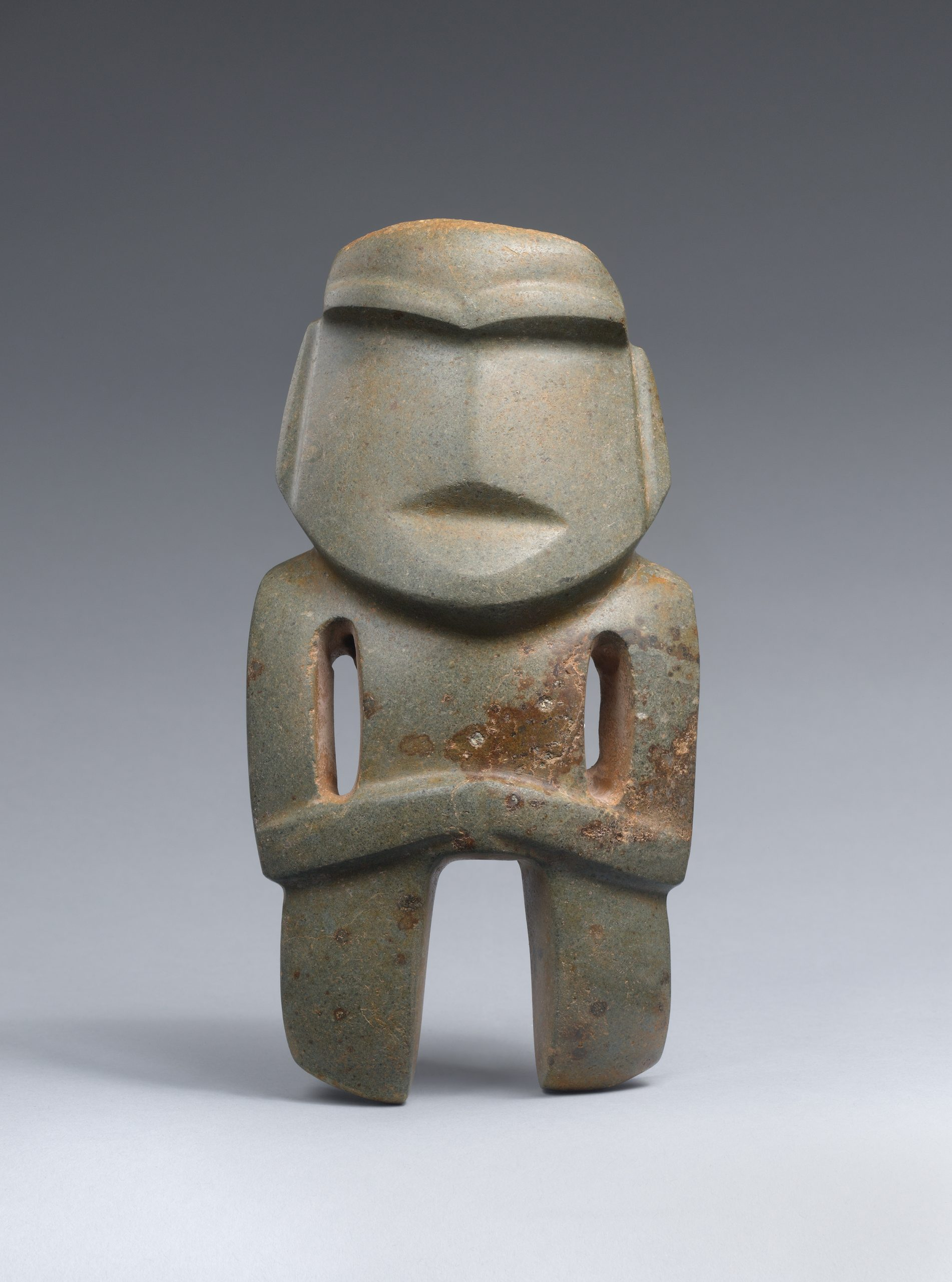 Stone sculpture of an abstracted standing figure with carved facial features, and arms resting across the torso.