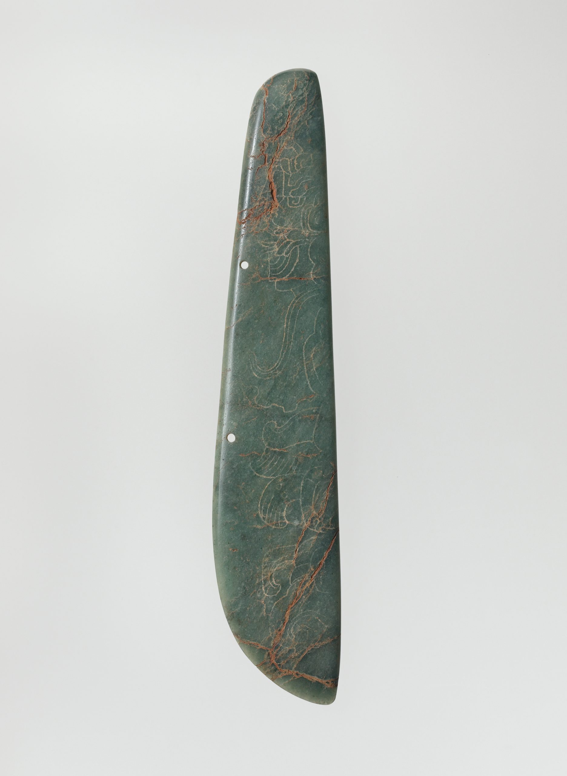 Pendant-like sculpture with engraved figures in elaborate feather headdresses and flowing garments.