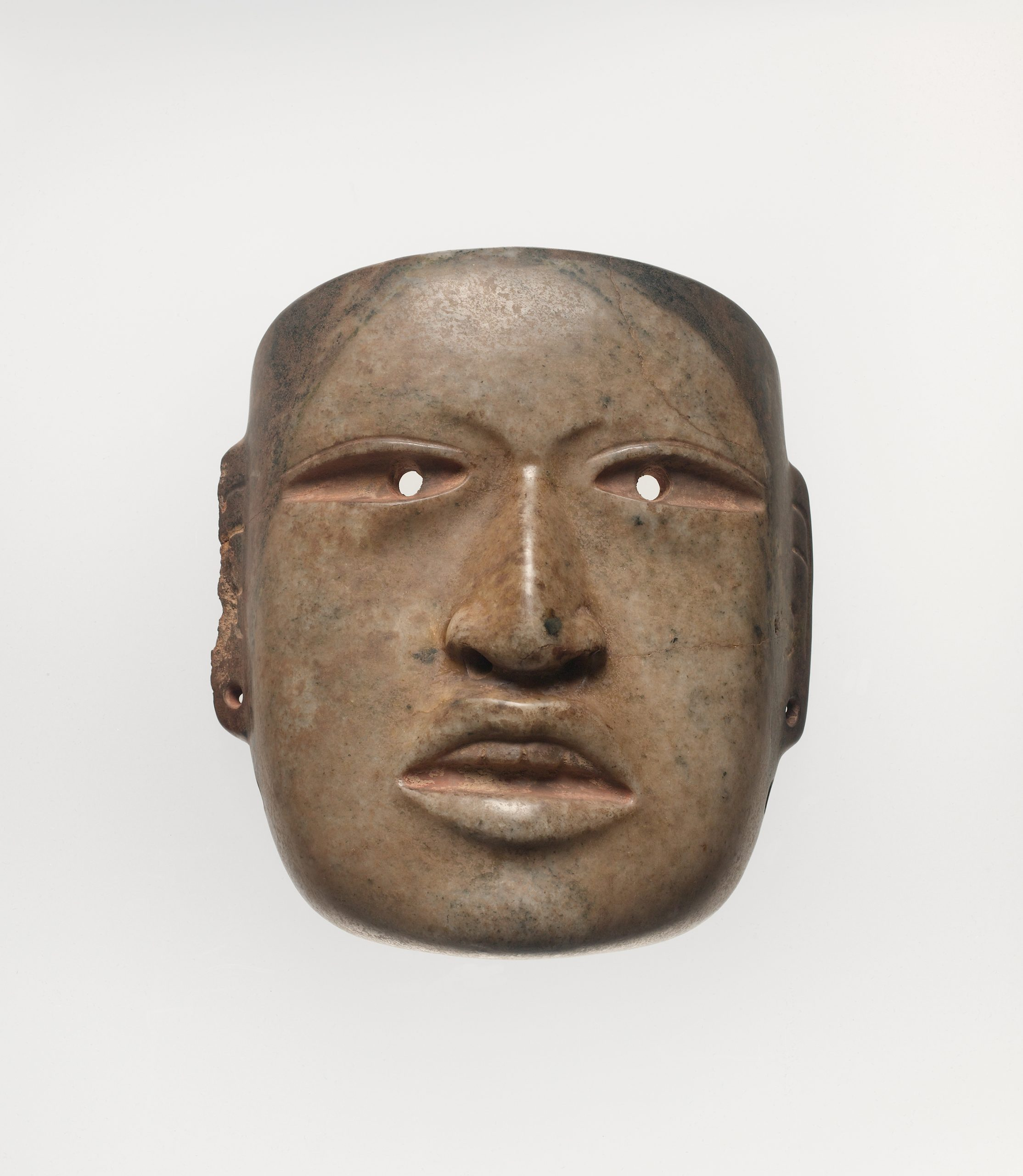 Ritualistic face mask with drilled eyes and ear spools, and a naturalistic mouth open to expose top teeth.