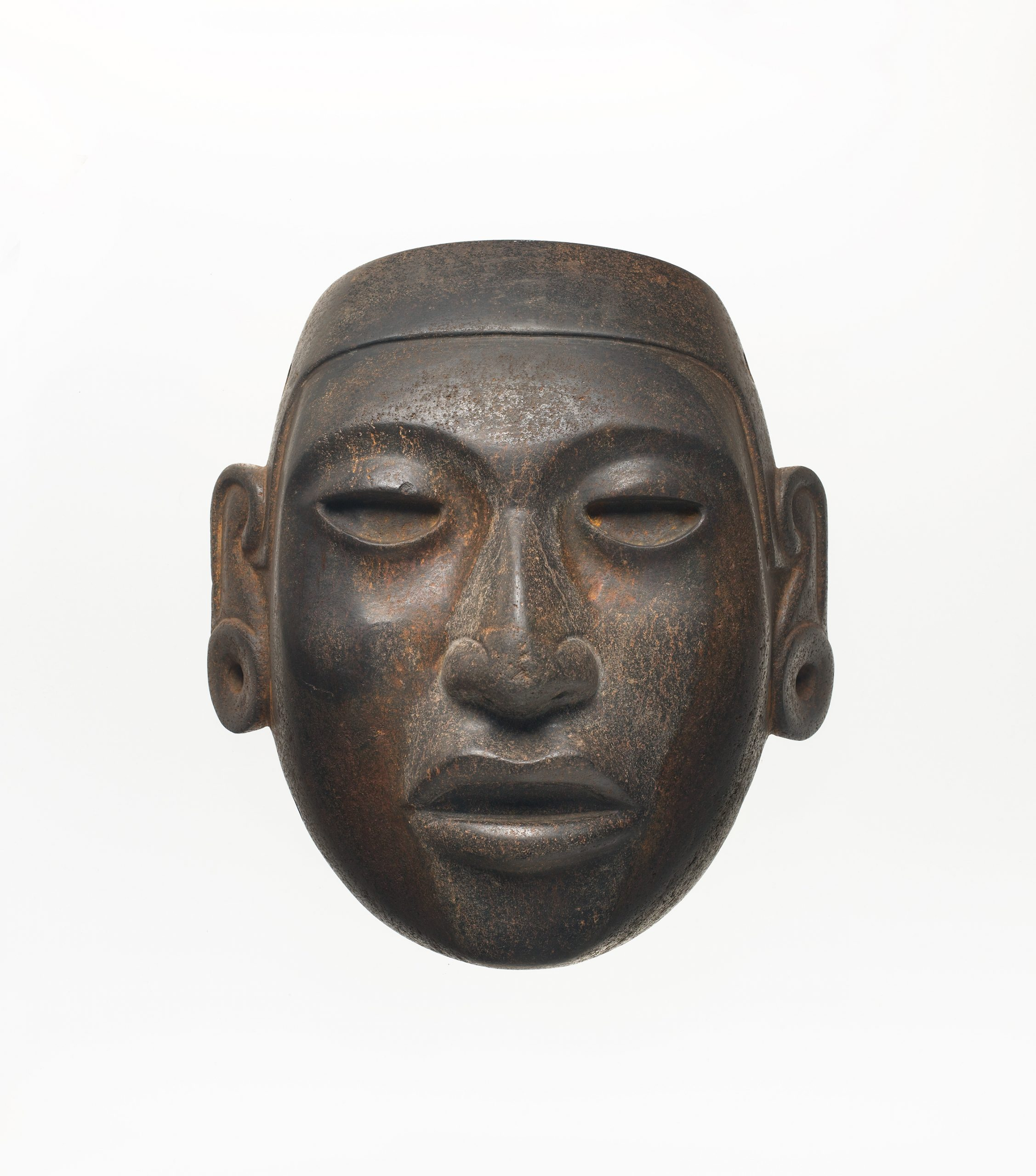 A brown mask with hollow eyes, a realistic mouth and nose, and pierced ear spools.