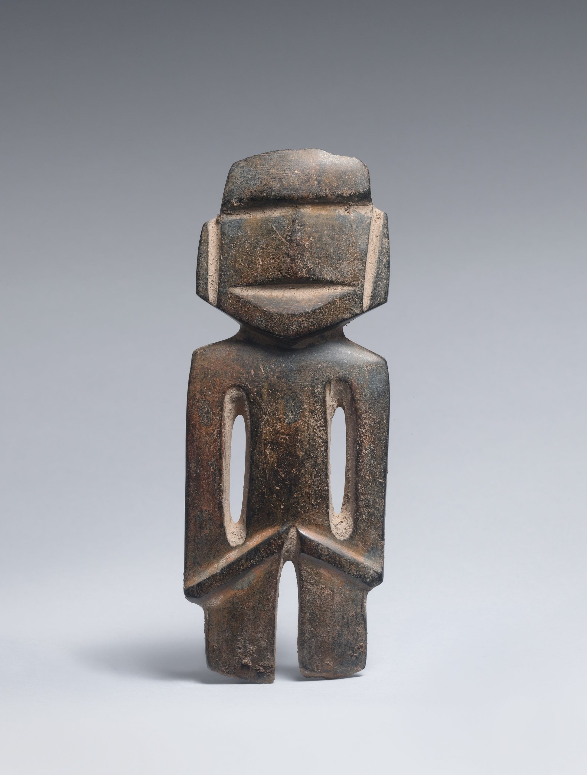Brown stone figure with geometric cuts and hollows indicating physical and facial features.