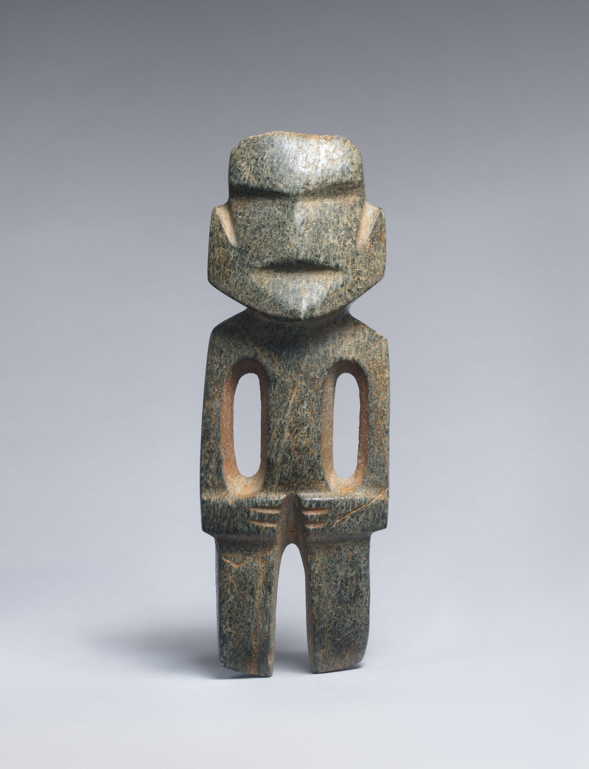 Stone figure with a broad rounded face, indentations for the nose and mouth, two hollows to form the torso and arms, and hands folded across the body.