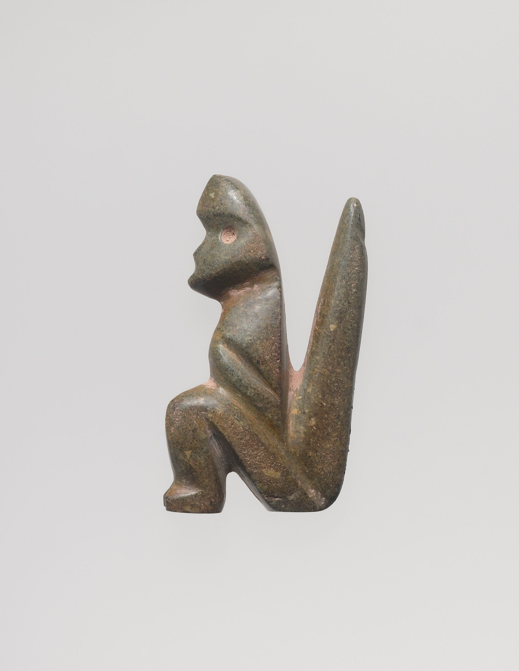 Standing abstract figure with large head, small drilled eyes, and barely carved out arms, and legs.