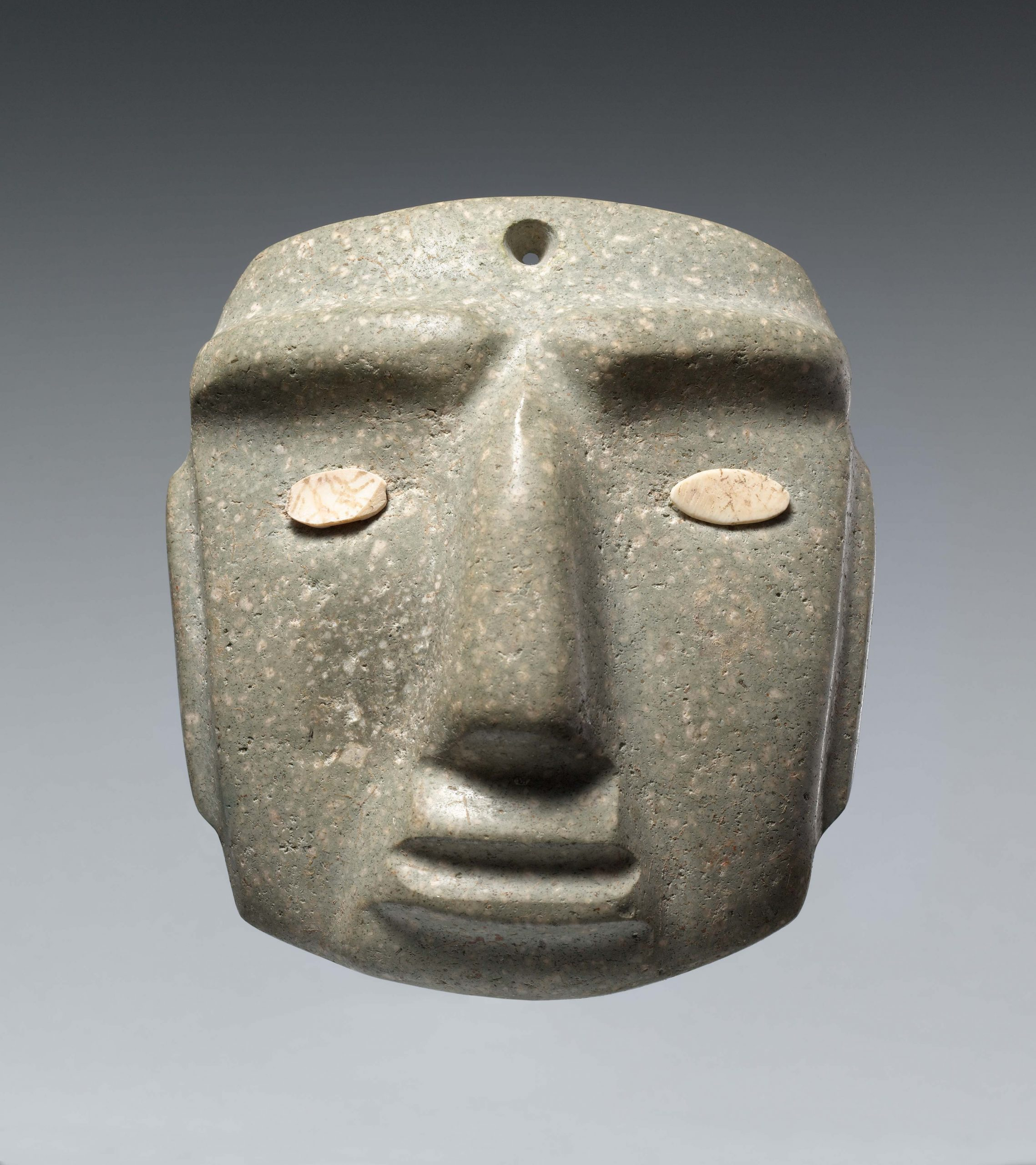 A stone mask with indented facial features and inlaid shell to represent the eyes.