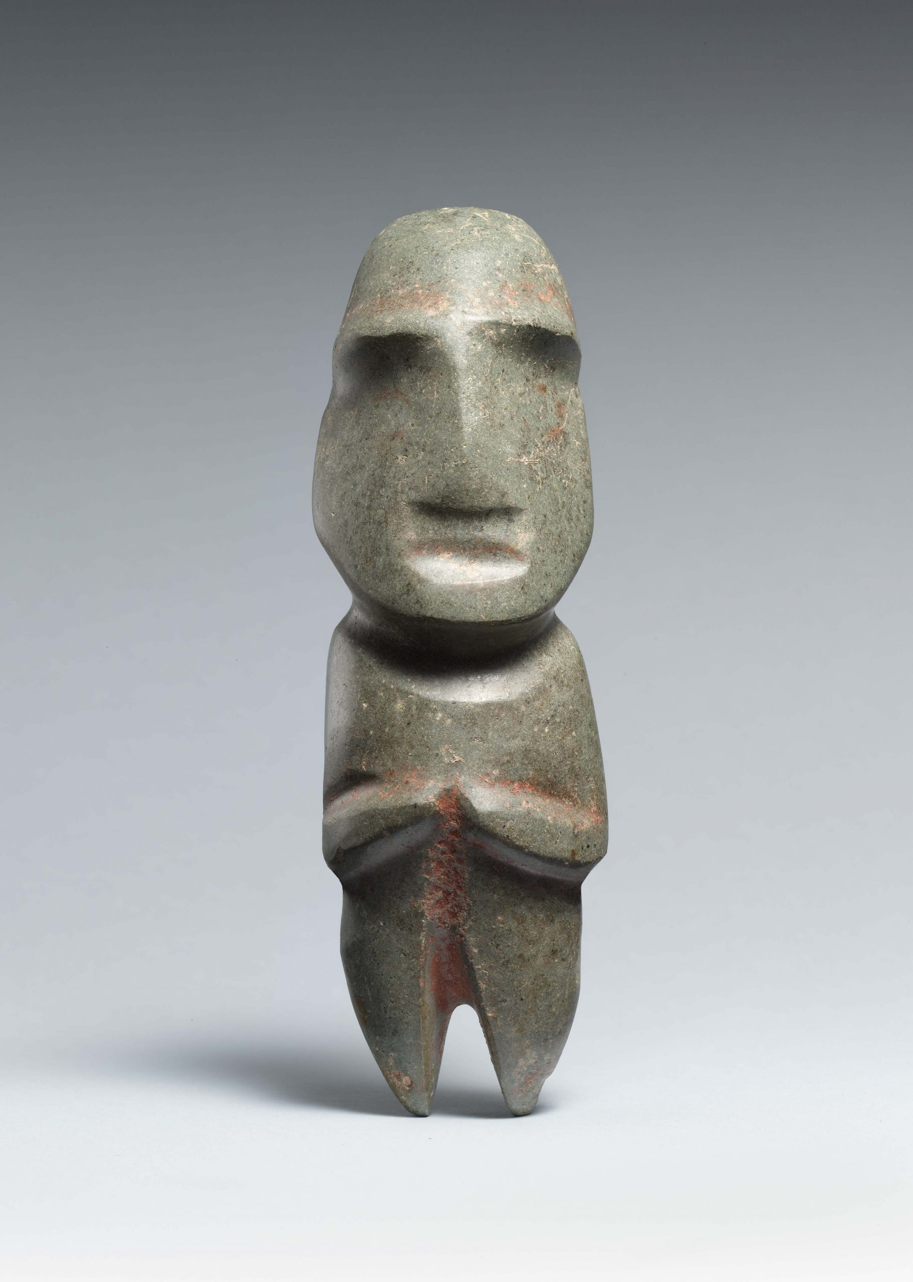 Abtract figure with arms crossed in front and a rounded head with T-shaped nasal and eyebrow ridges.