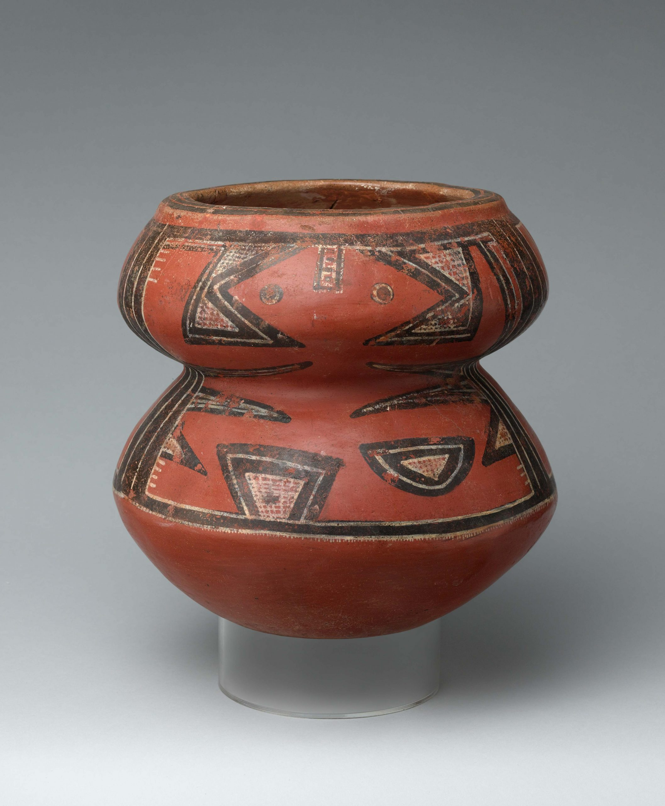 A Kewa jar painted beige and black, with two bands of design, and a rust-colored bottom.