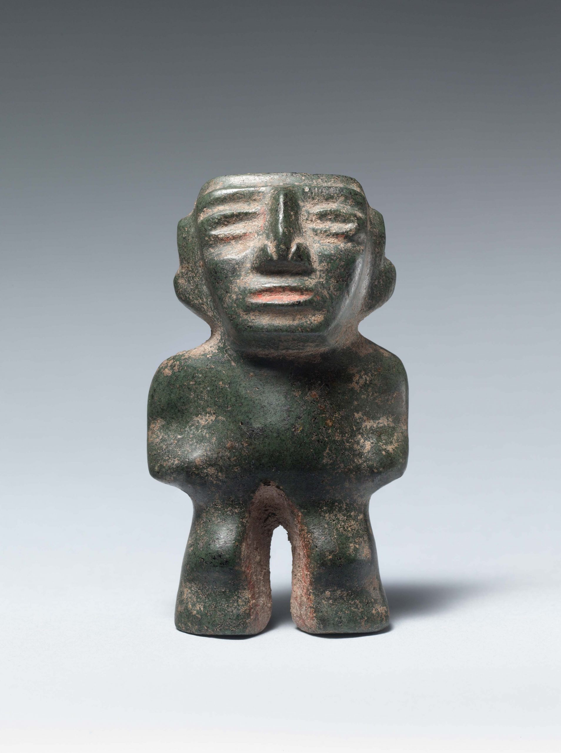 Abstract green stone standing figure with a large pointed nose and indented facial features.