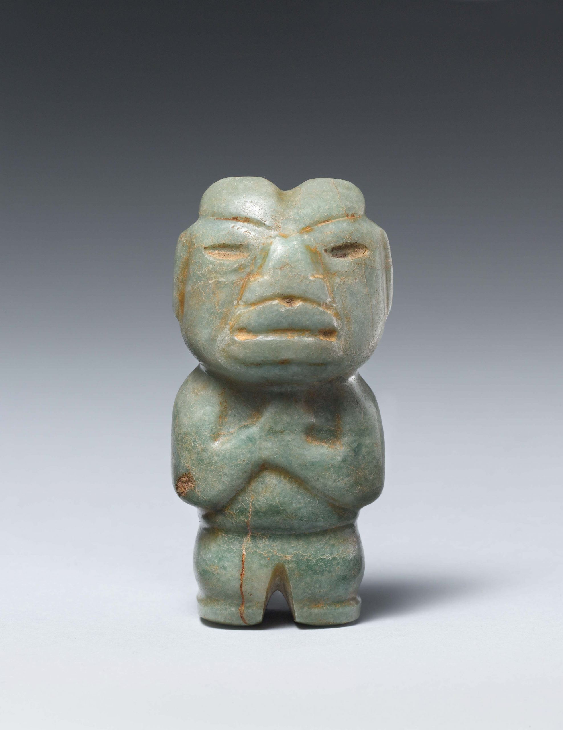 Standing stone figure of a man with stylized geometric facial features, almond-shaped eyes and rounded body parts.