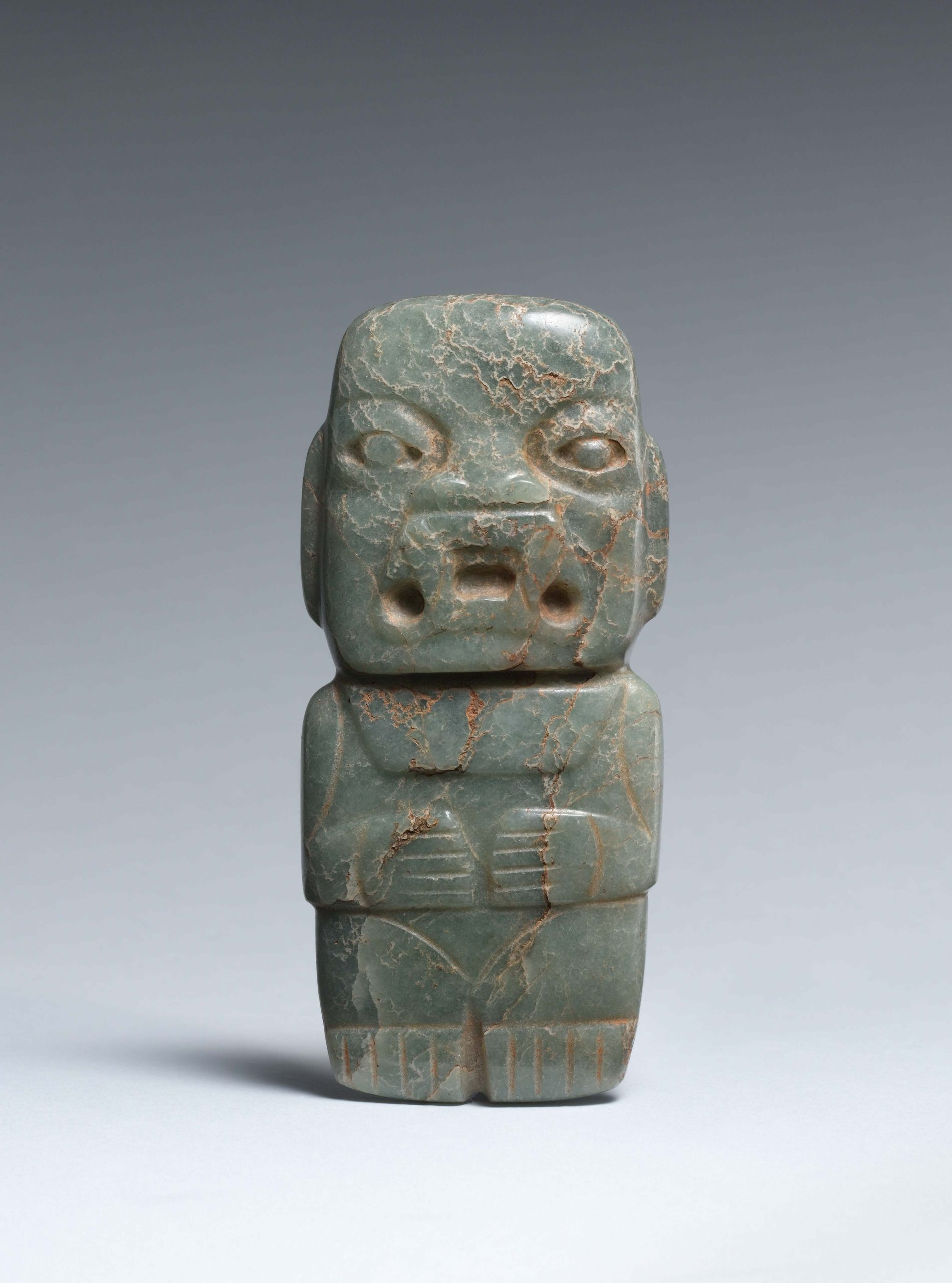 Male figure with almond-shaped eyes, cuts indicating arms, hands resting on knees across the torso, and a large open mouth with fangs.