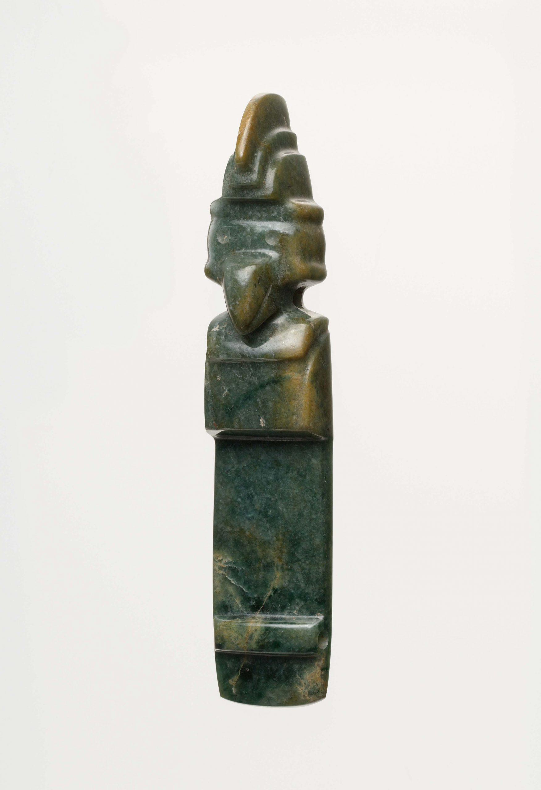 A dark green and yellow jade celt featuring a Costa Rican bird wearing three-tiered crown.