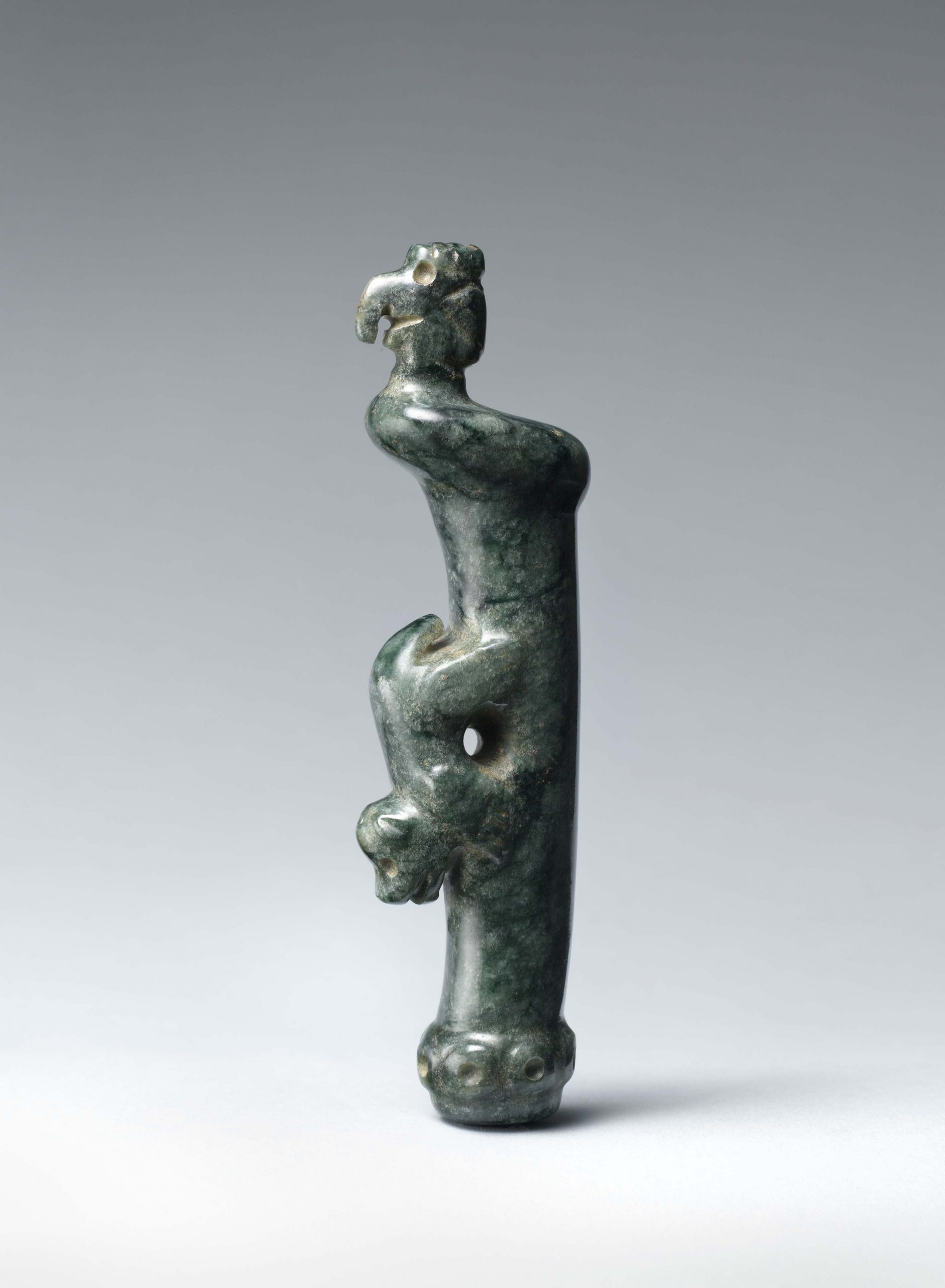 A long vertical pendant with a canine figure at the center of the celt and an avian effigy emerging at the top.