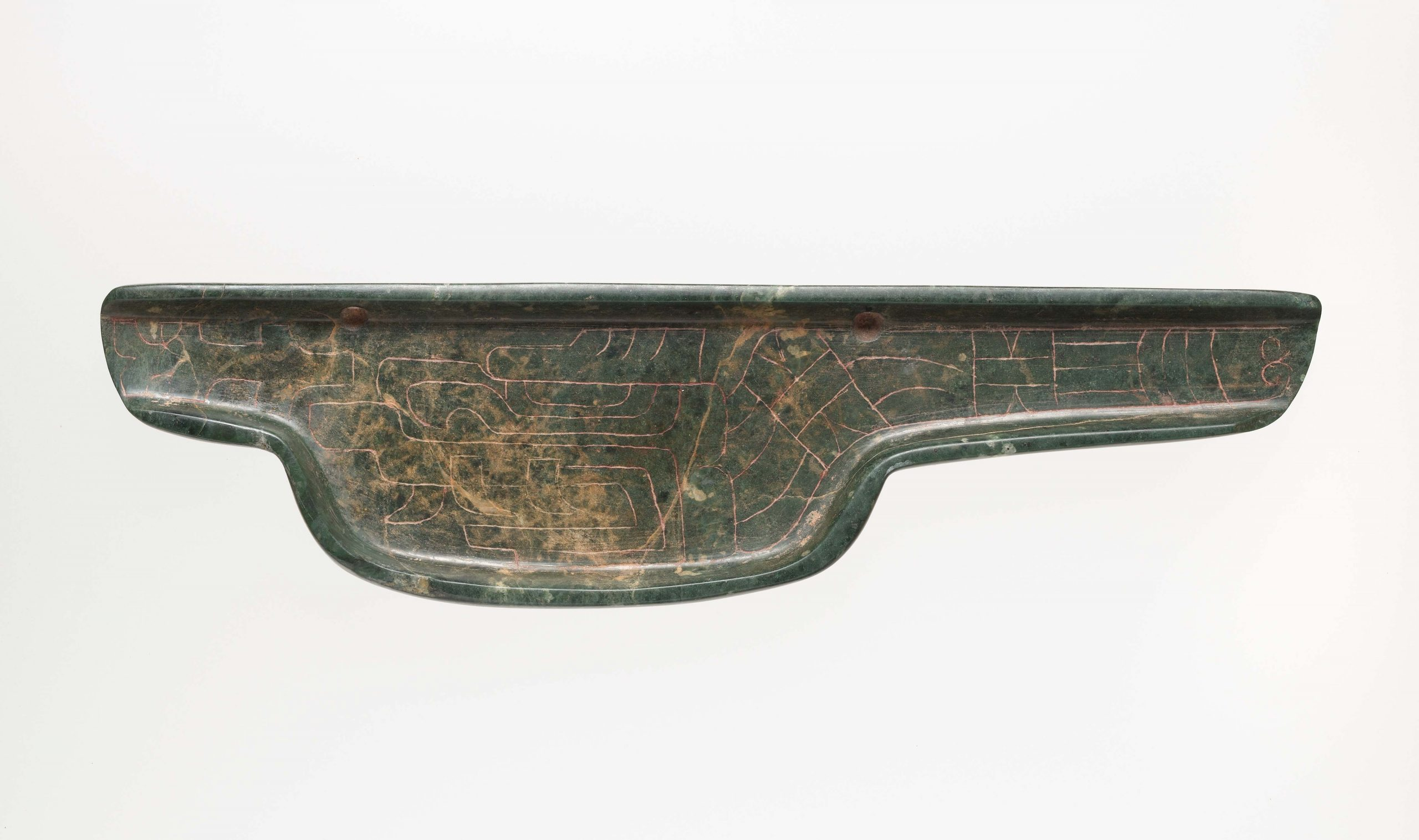 Flat, dark green celt with engraved imagery.