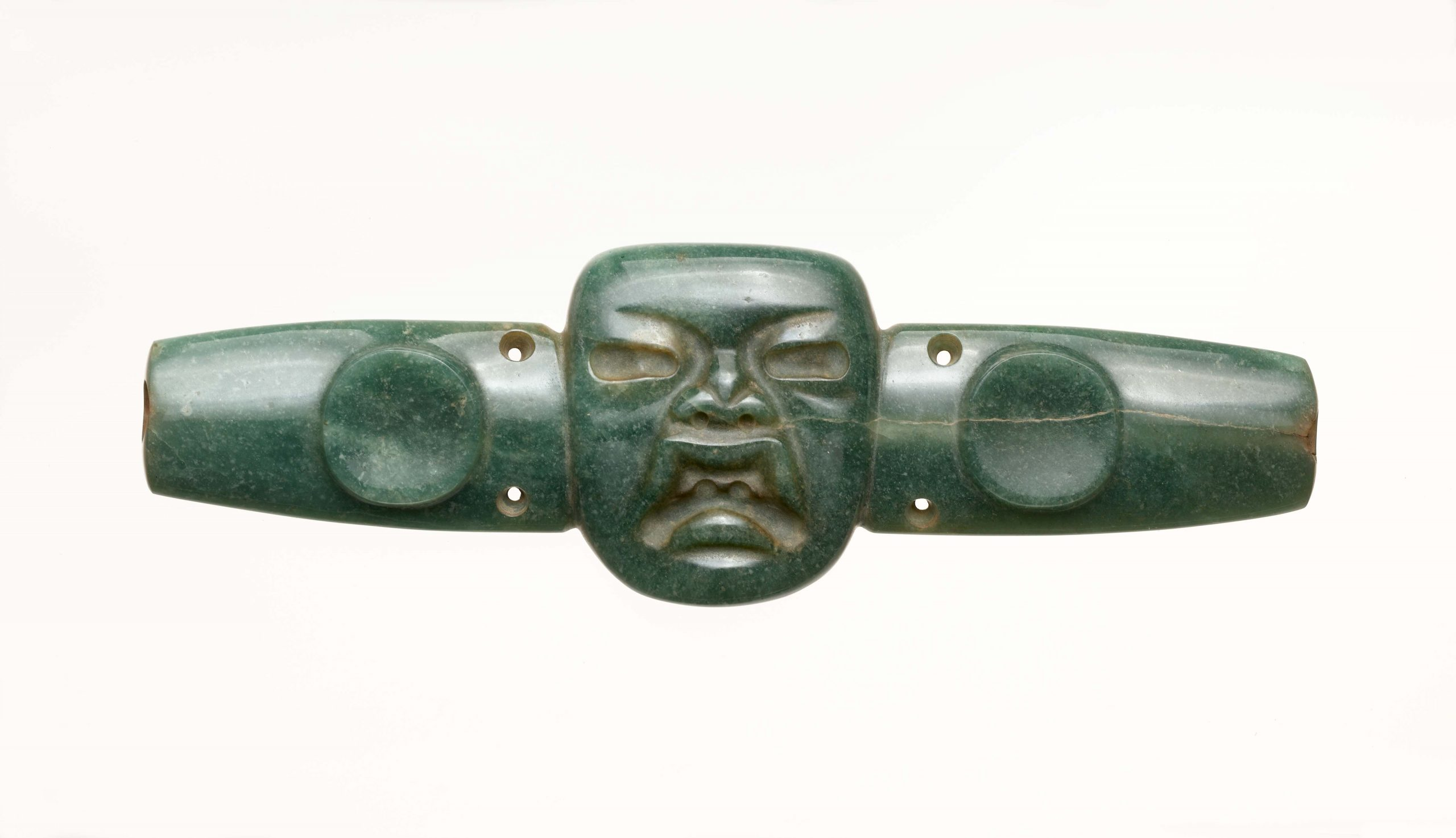 Long, horizontal, blue-green chest ornament with face in relief in center.