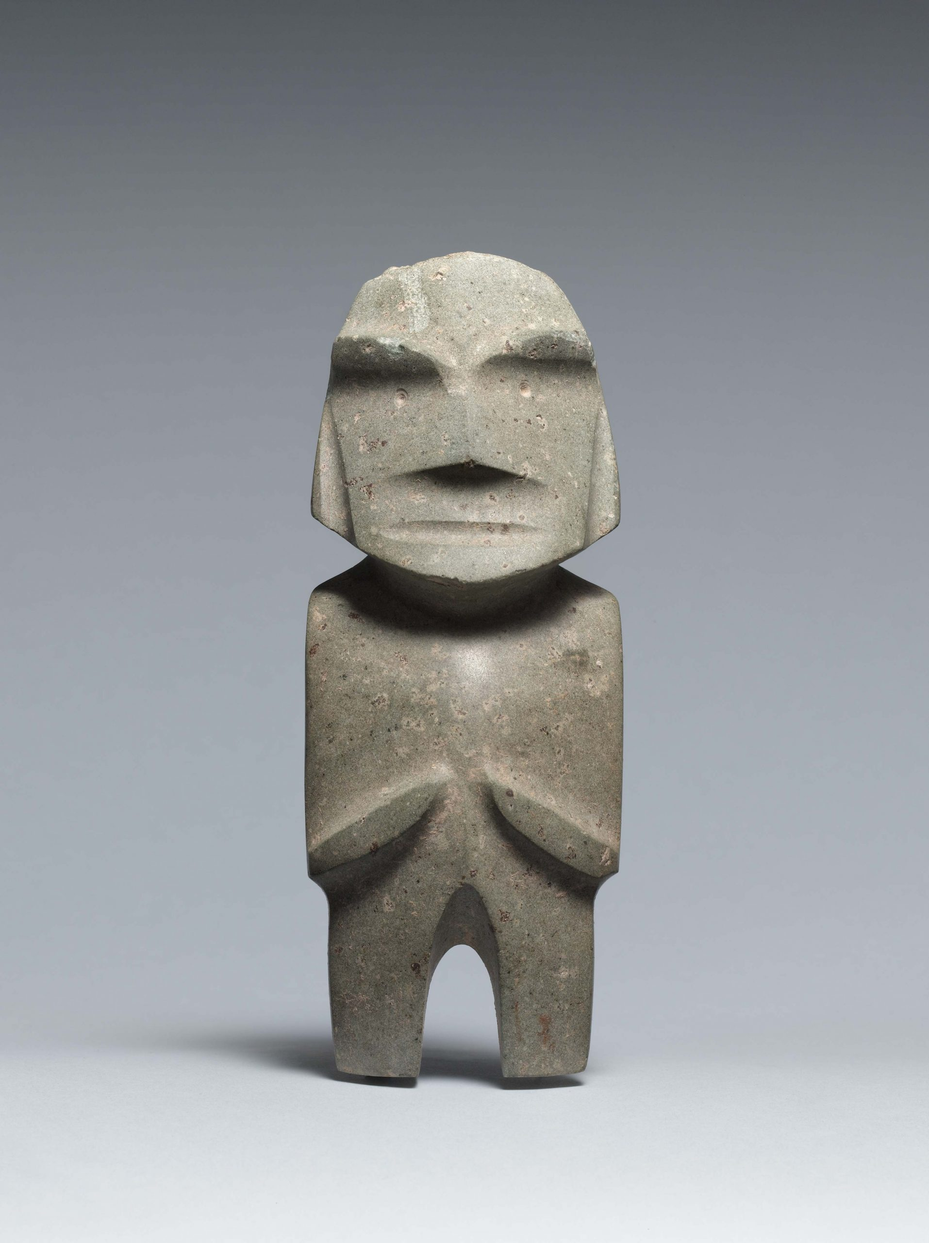 Abstract standing figure with indented facial features and pointed nose, arms at the side and folded at the ribs.