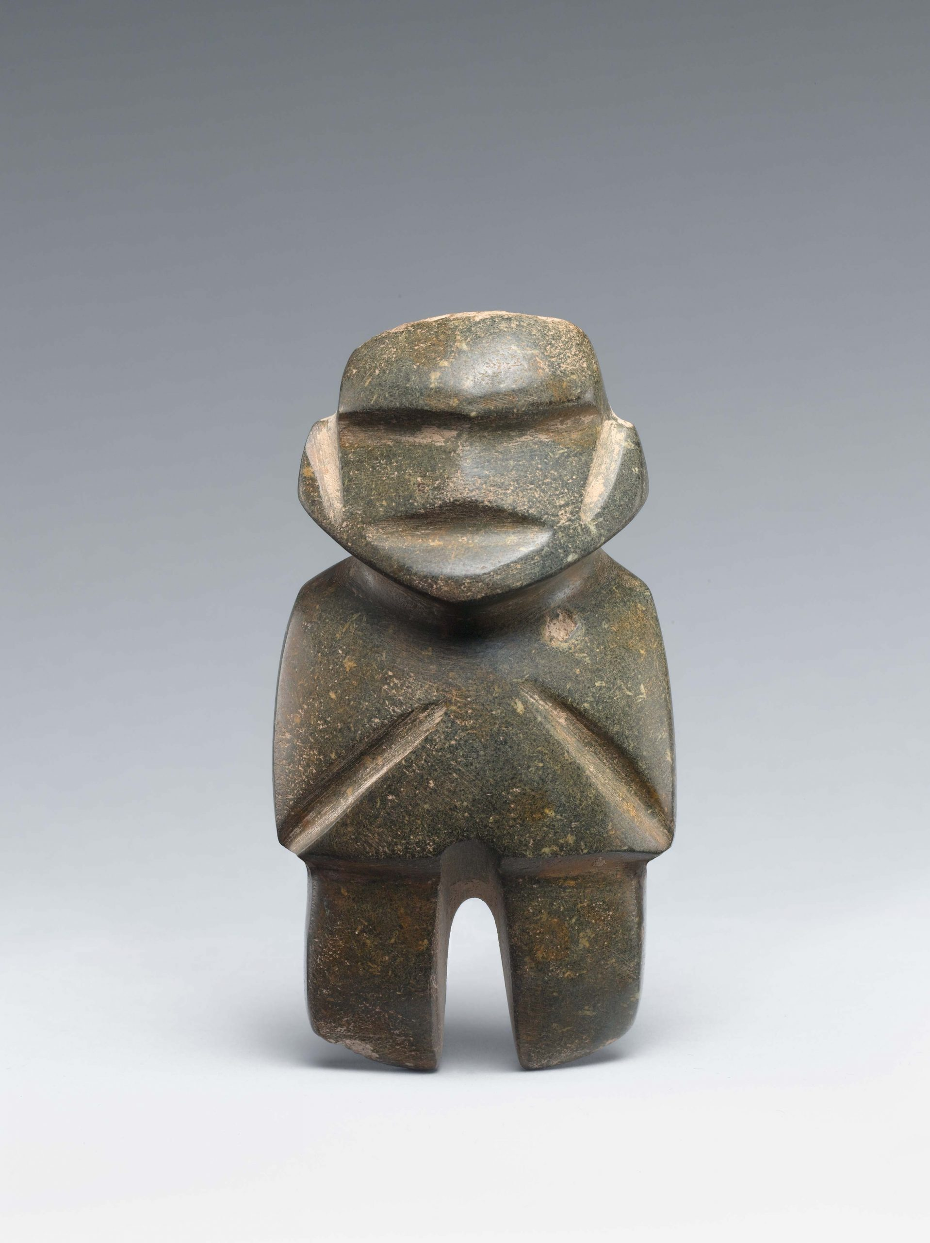 Abstract dark-green standing stone figure with indented features, including eyes, ears, mouth, arms, and legs.