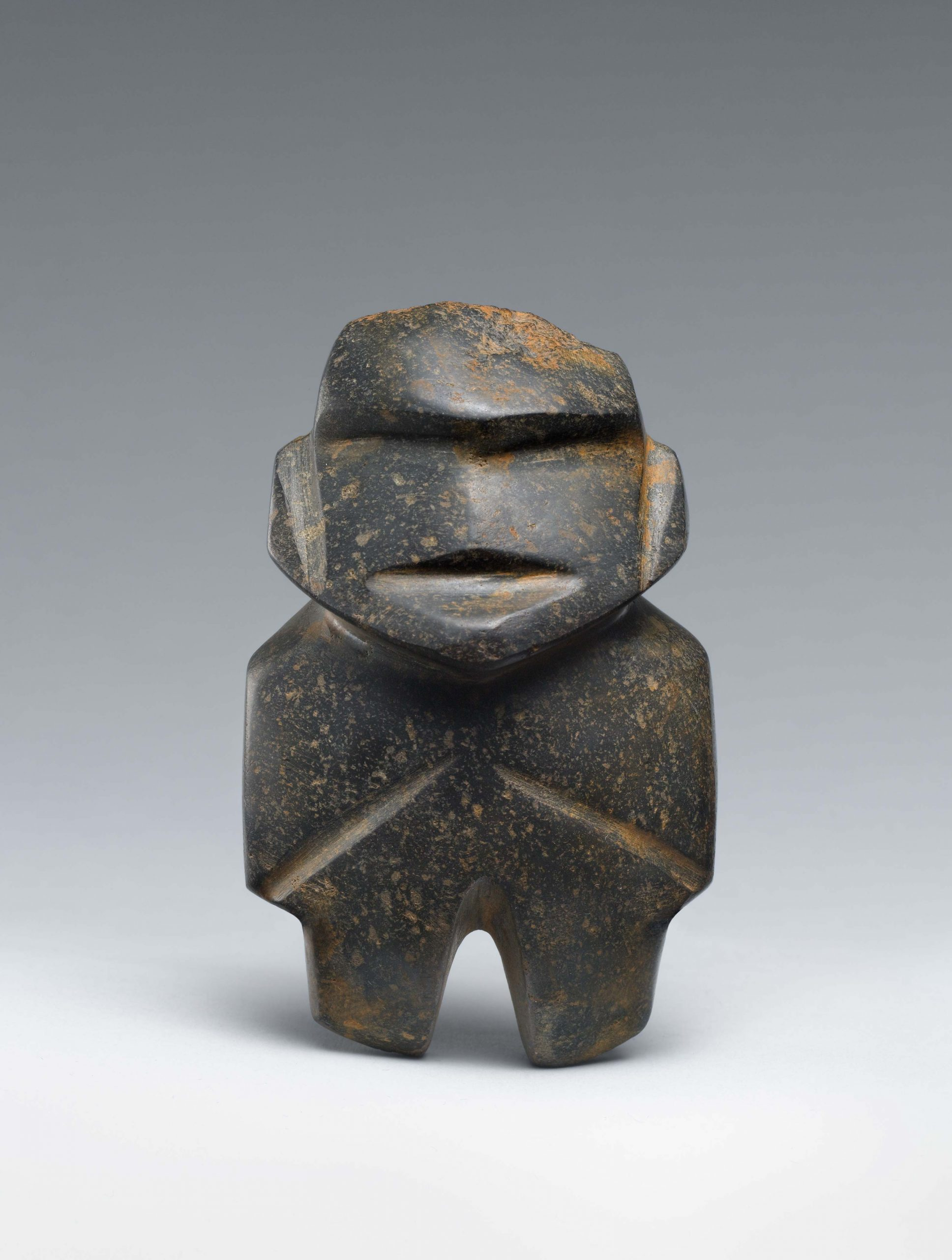 Abstract stone figure with vertical cuts to represent facial features, arms, legs, and prominent eyebrows.