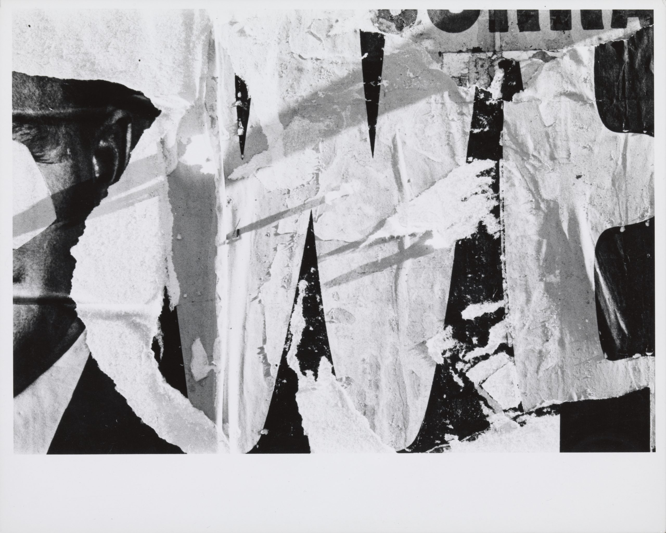 Black and white photograph of weathered and torn advertisements.