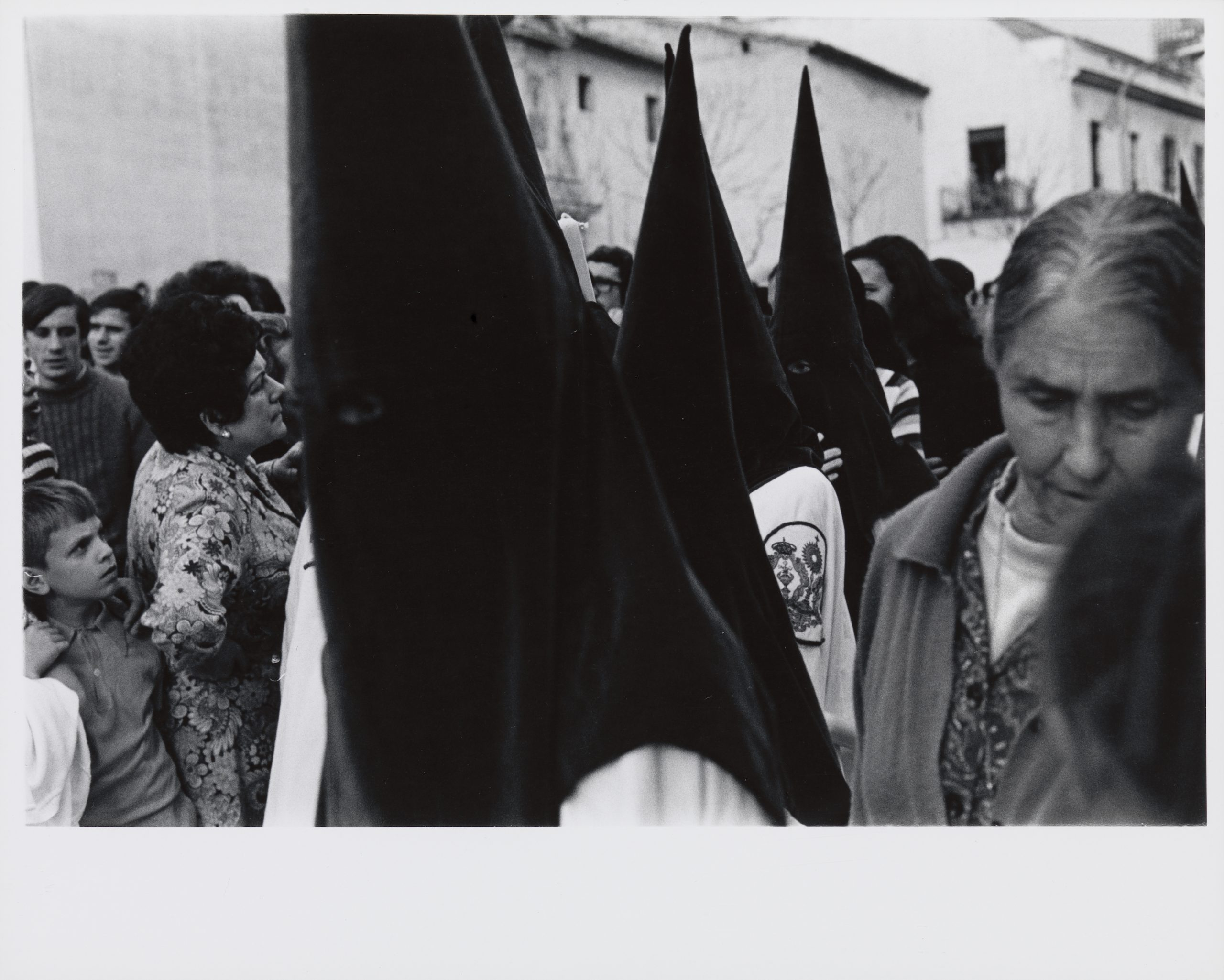 A black and white photograph of a procession of hooded penitents in Seville, Spain during Holy Week.