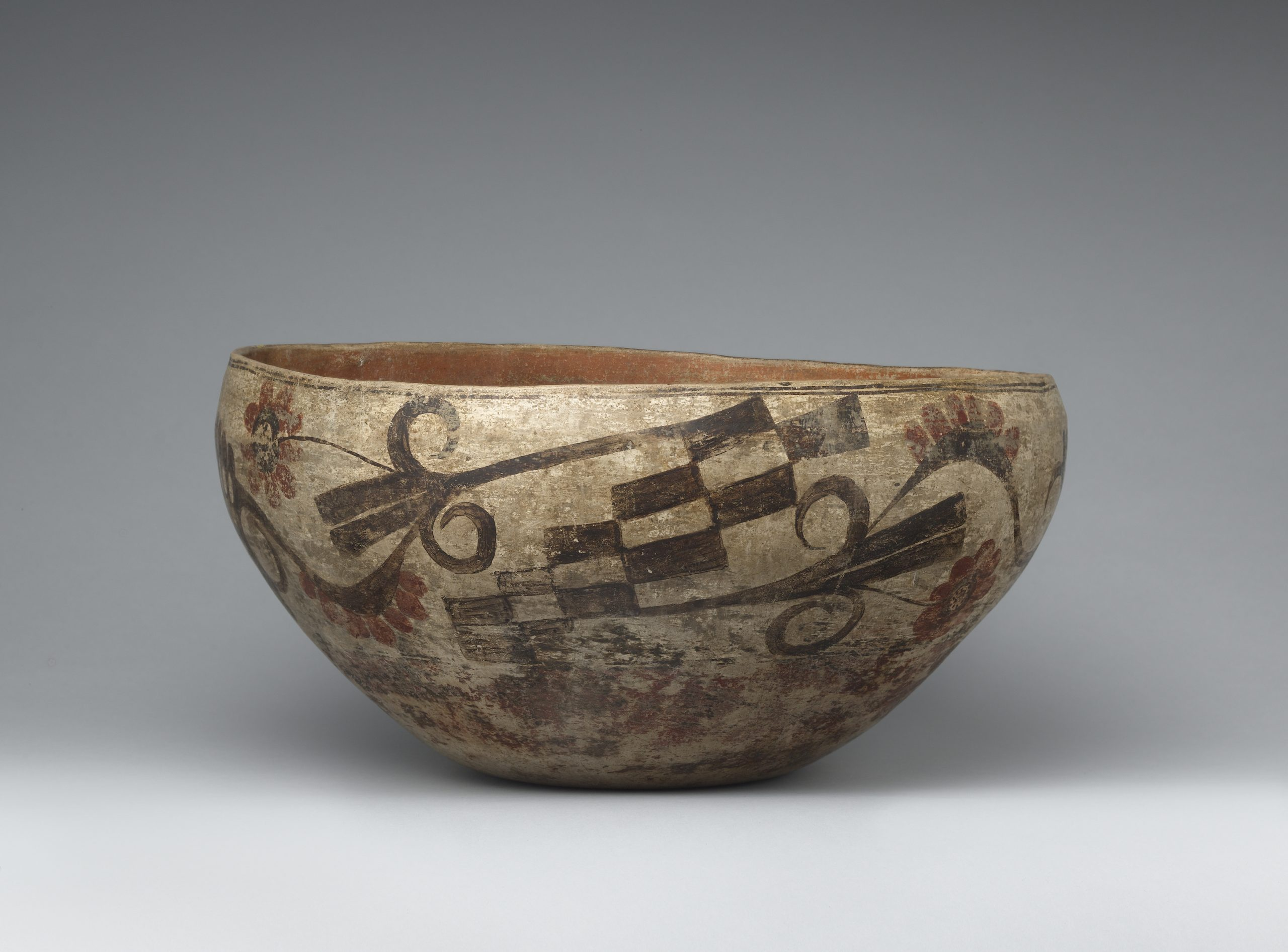 An Acoma bowl with checkered design and floral patterns in brown and red.