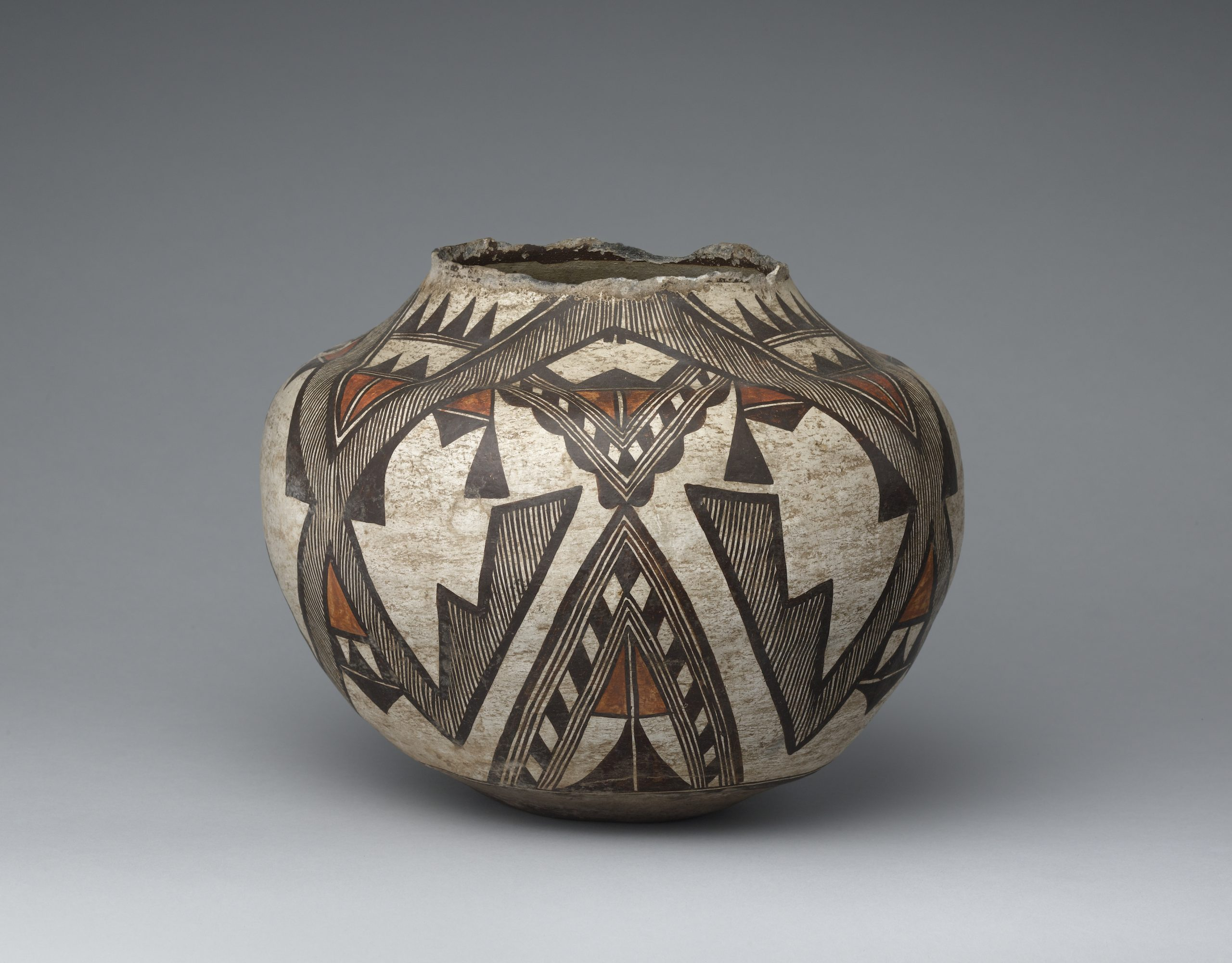 A Zuni olla with a stylized wing design primarily composed of lines and triangular shapes.