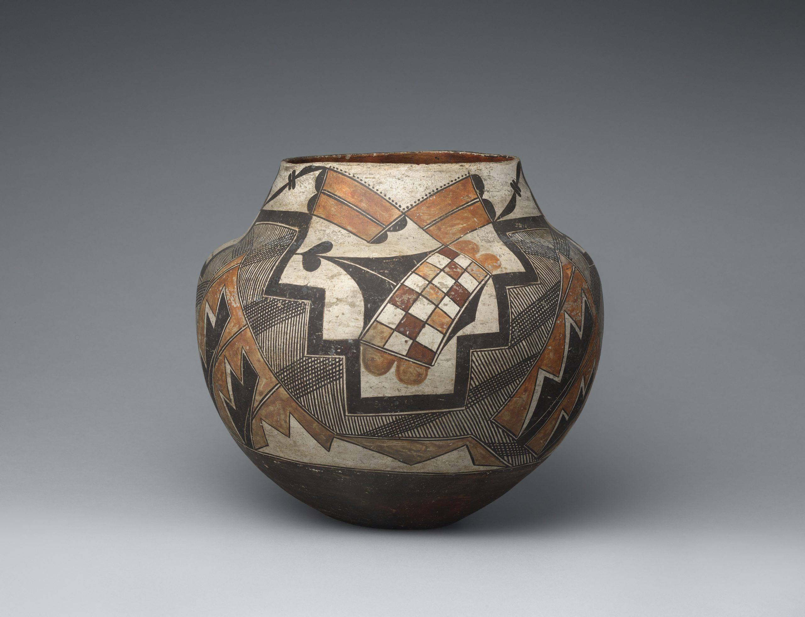 A four-color olla decorated with geometric shapes and checkered designs.