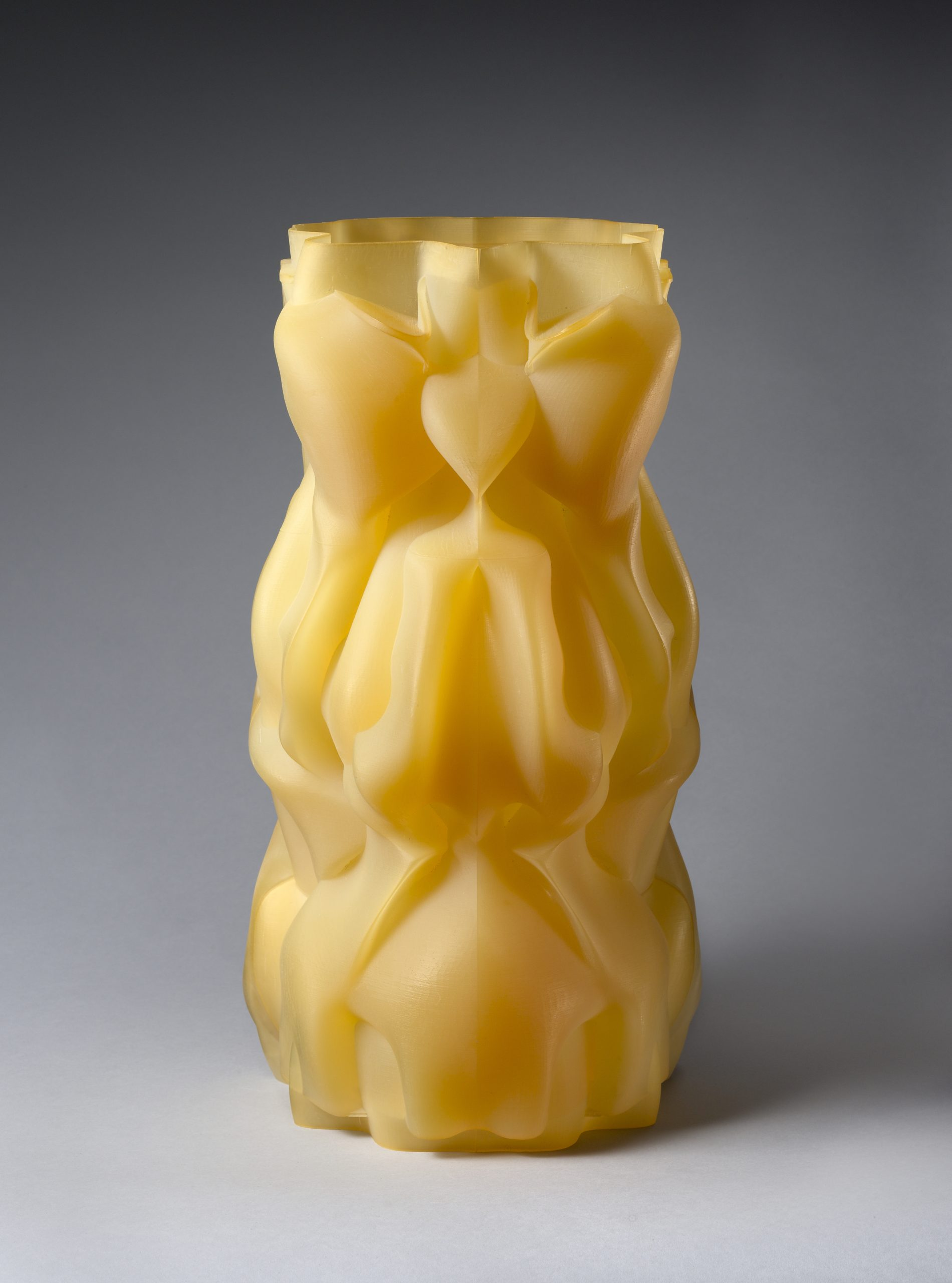 Translucent yellow abstract sculpture with multiple folds.