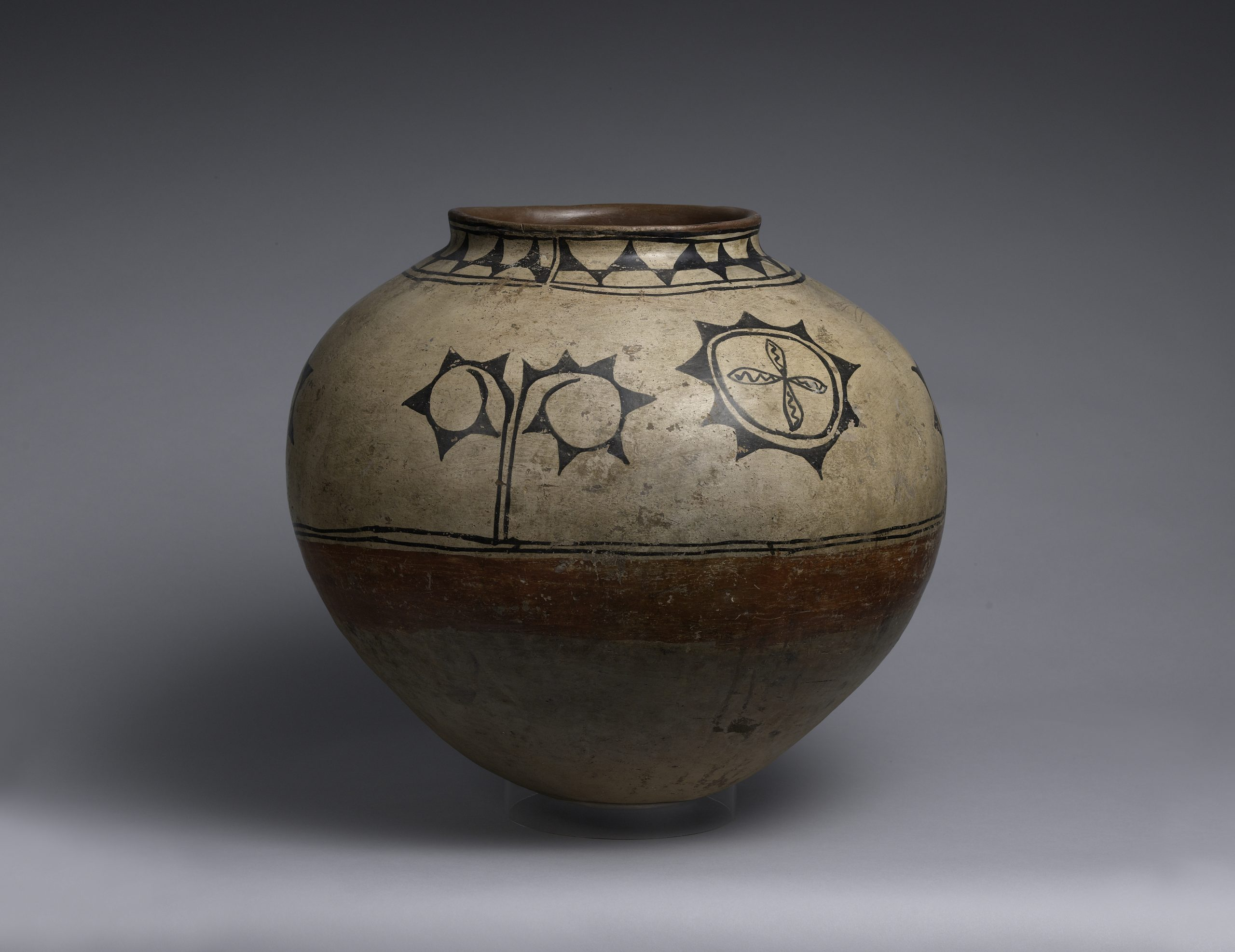 A Cochiti storage jar decorated with geometric and plant designs.