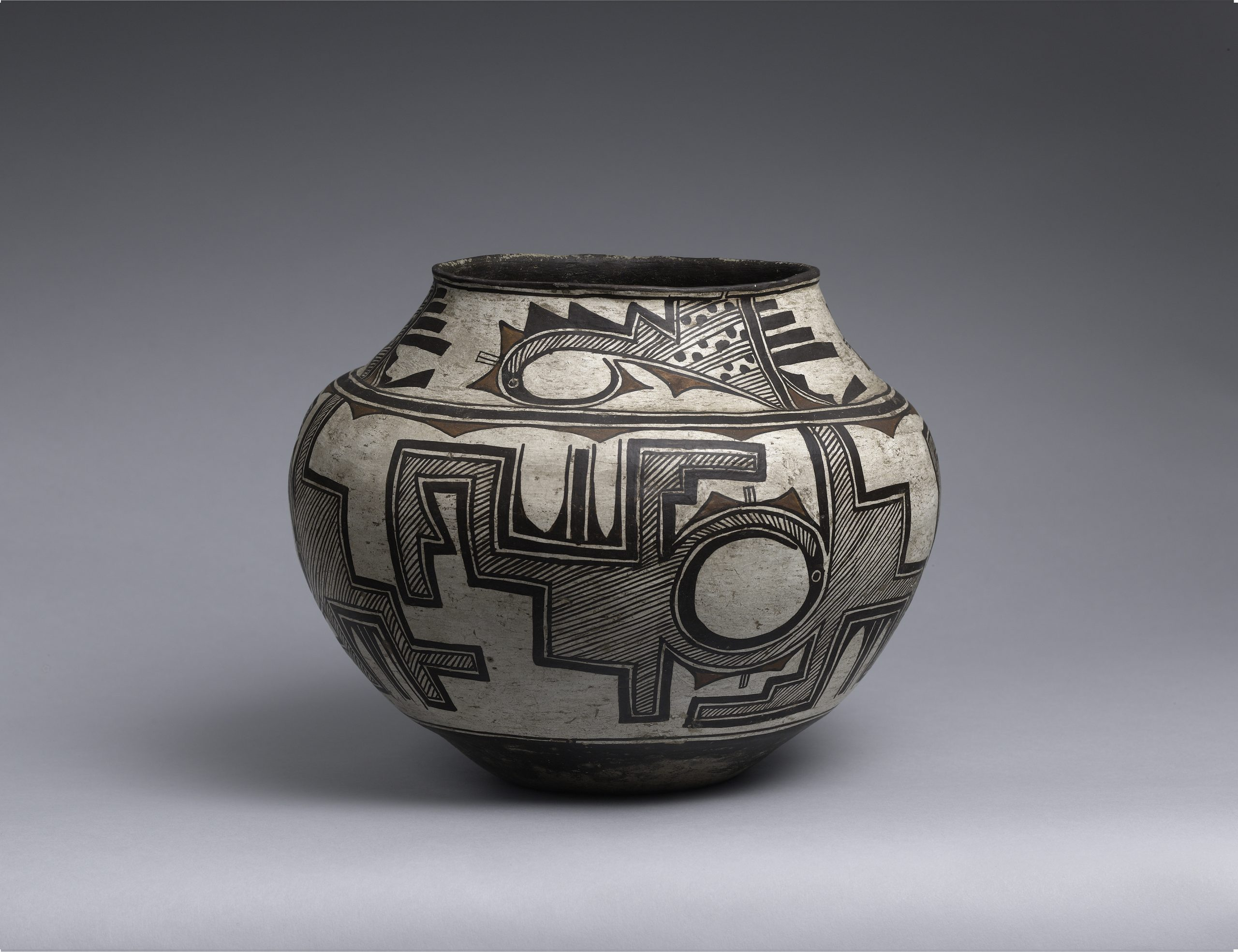 A Zuni olla with two bands of continuous black geometric patterns.