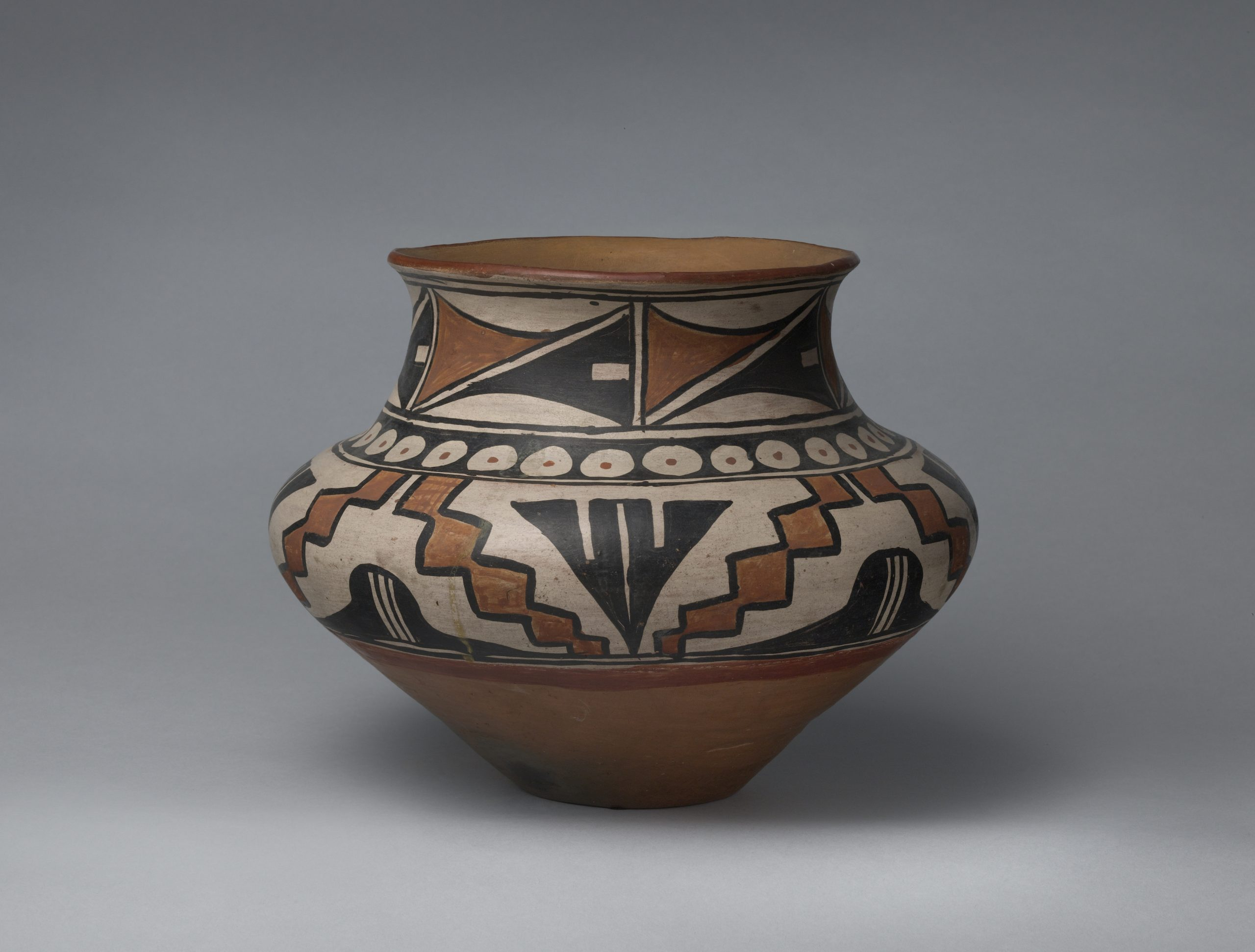 A San Ildefonso jar with three bands of black and brown geometric designs.