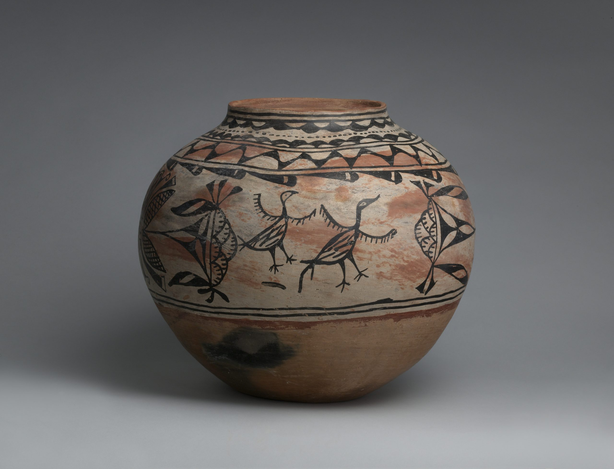 A Tesuque jar with stylized bird designs.