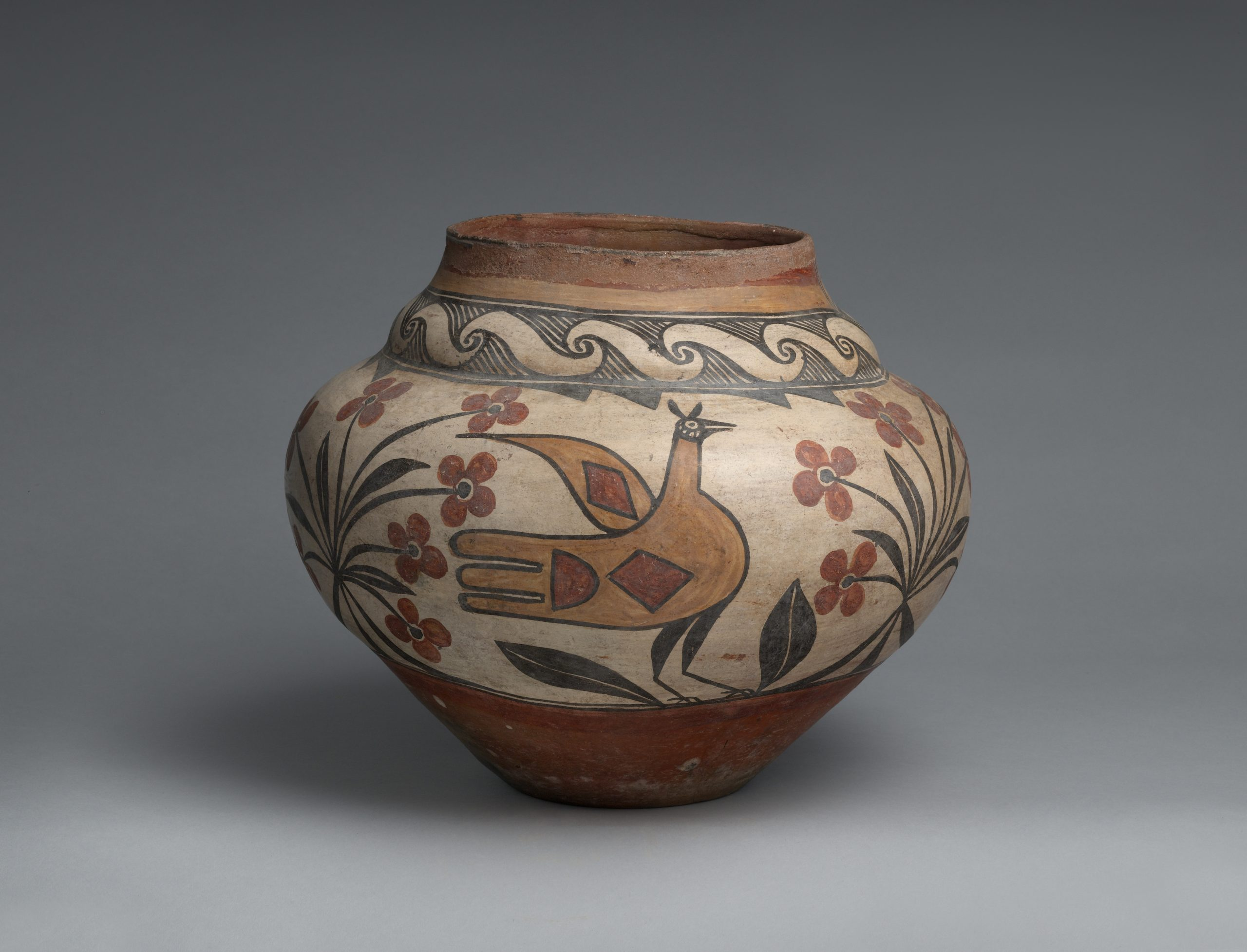 A Zia pot with a large bird and flowers painted in brown, red, and black.