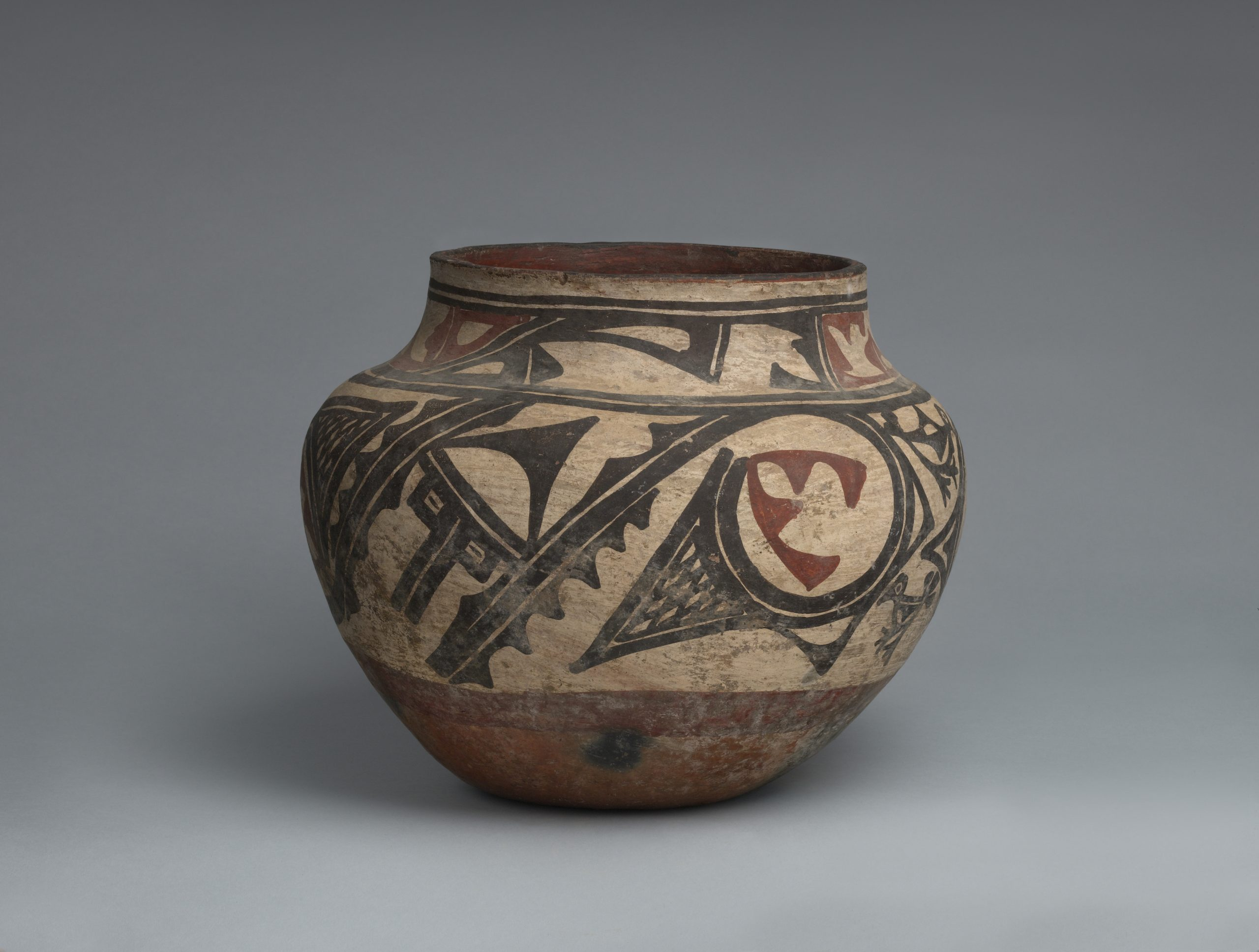 A Zia jar with two bands of abstract geometric designs in black and rust.