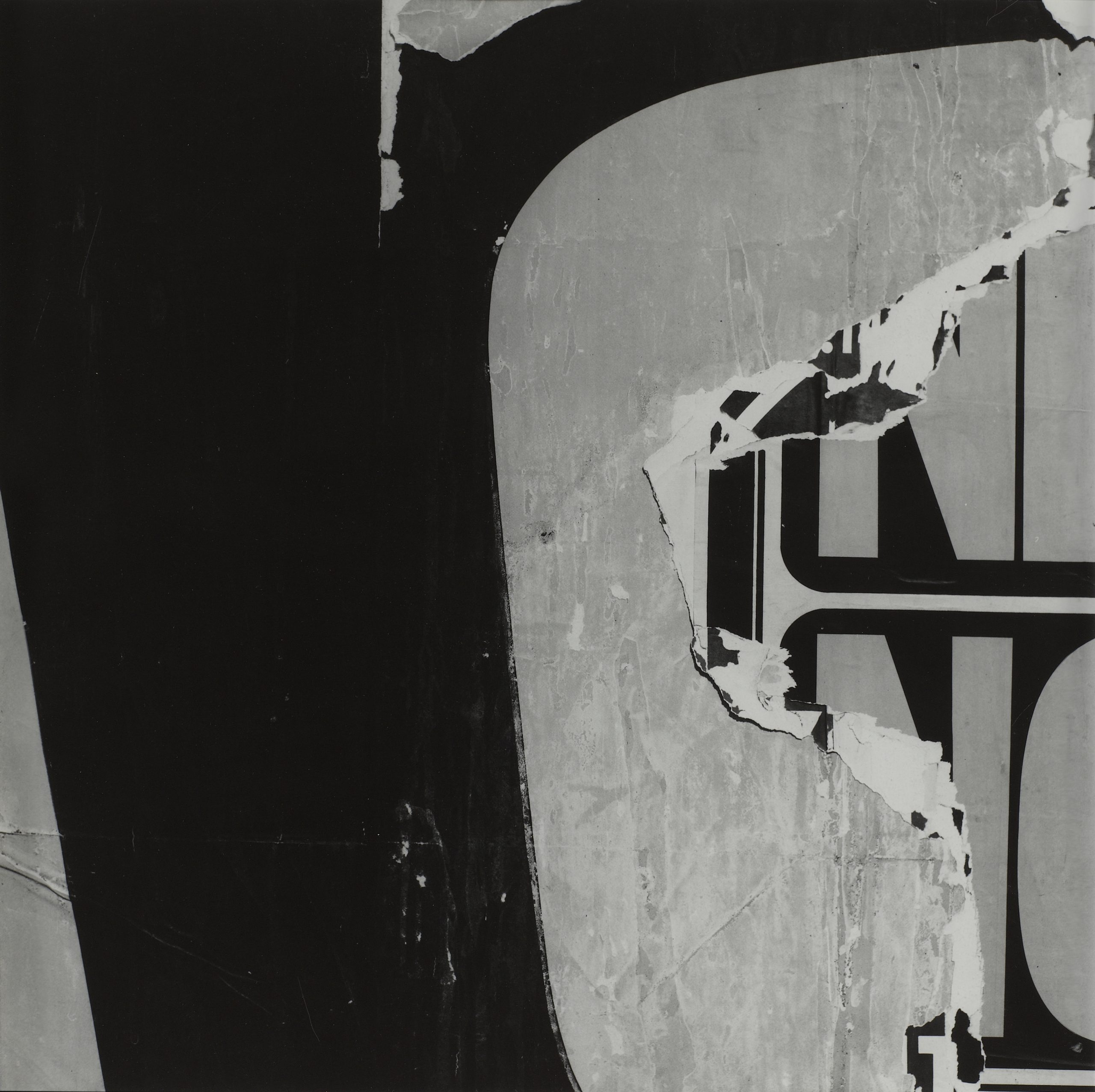 Black and white photograph of layered torn signs that reveal an obscured 'NO' present on the sign underneath.