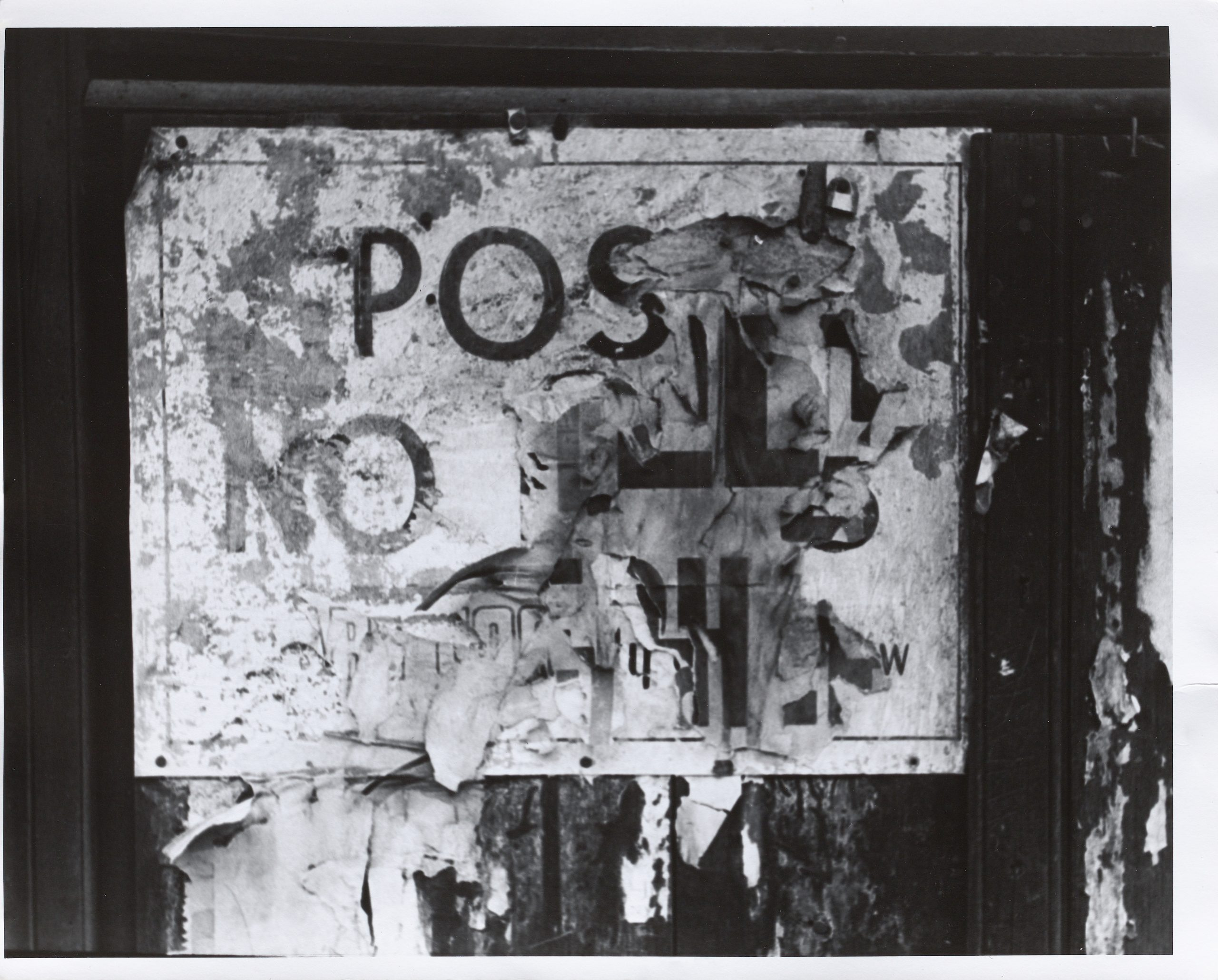 "A black and white photograph of layered torn signs with the distinguishable words ""post"" and ""no"" remaining."
