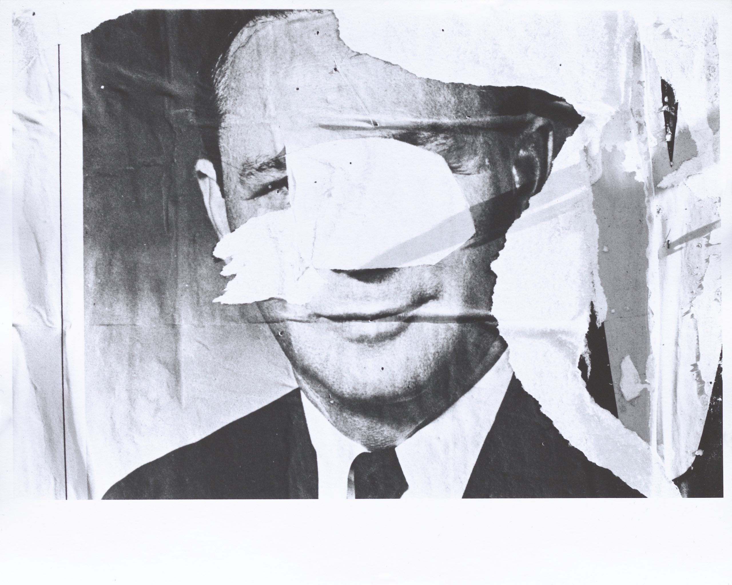 Black and white photograph of layered and torn signs that include the face of a man that has been torn leaving only a fragment of his face.