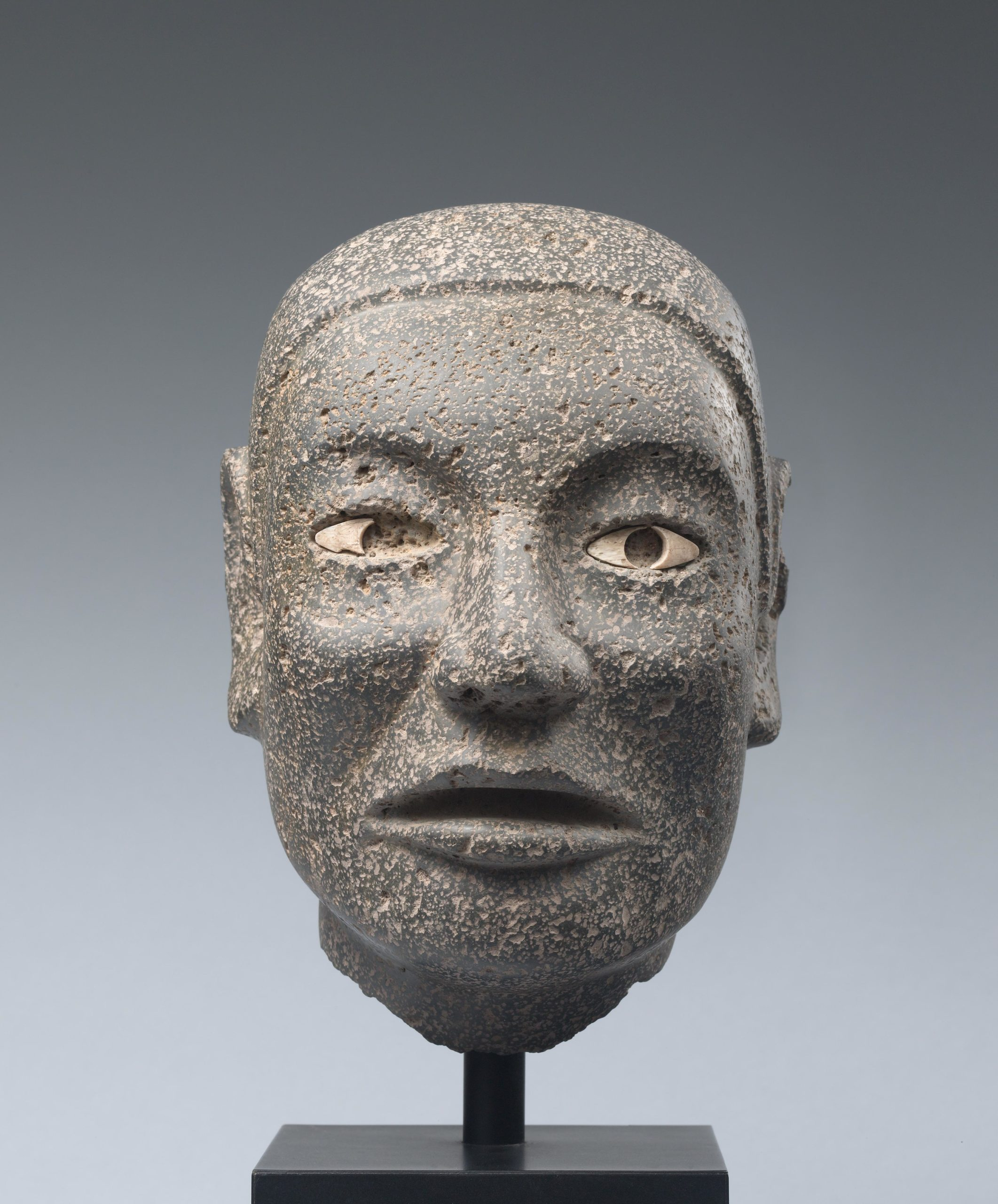 Naturalistic stone carving of a male head with ornamented inlaid eyes.