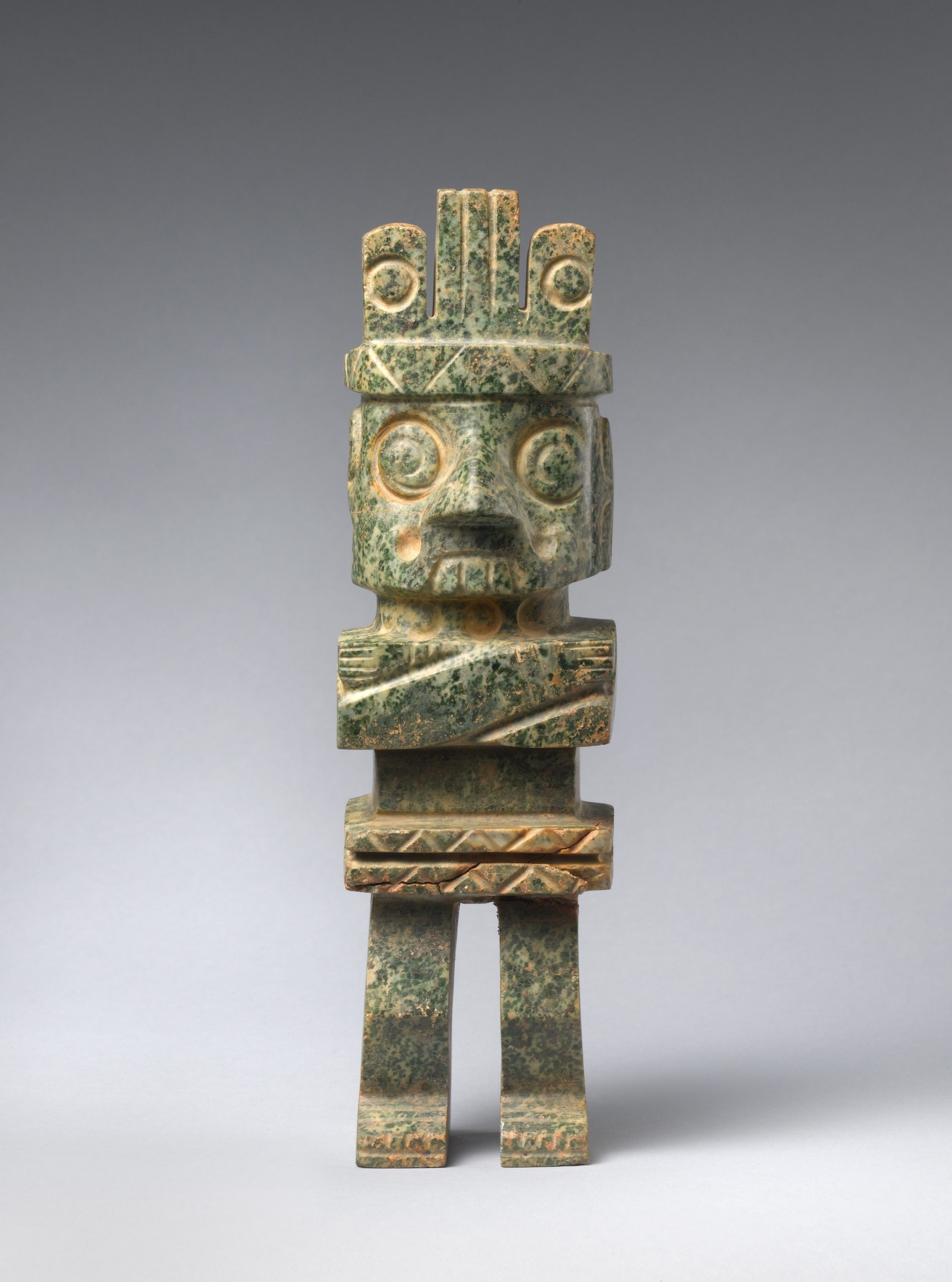 Standing stone figure with large goggle-like eyes, a curled lip, large teeth, folded arms wearing a headdress.