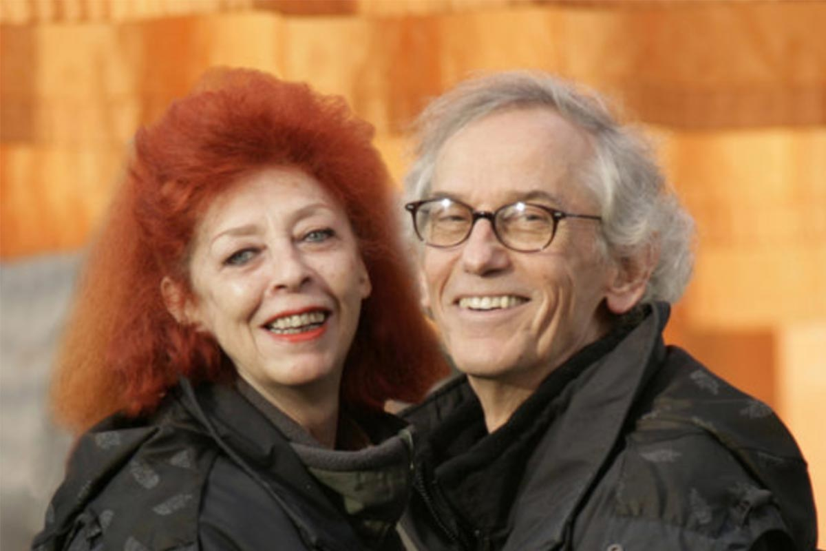 A photo of Christo and Jeanne-Claude in front of orange flags in New York City.